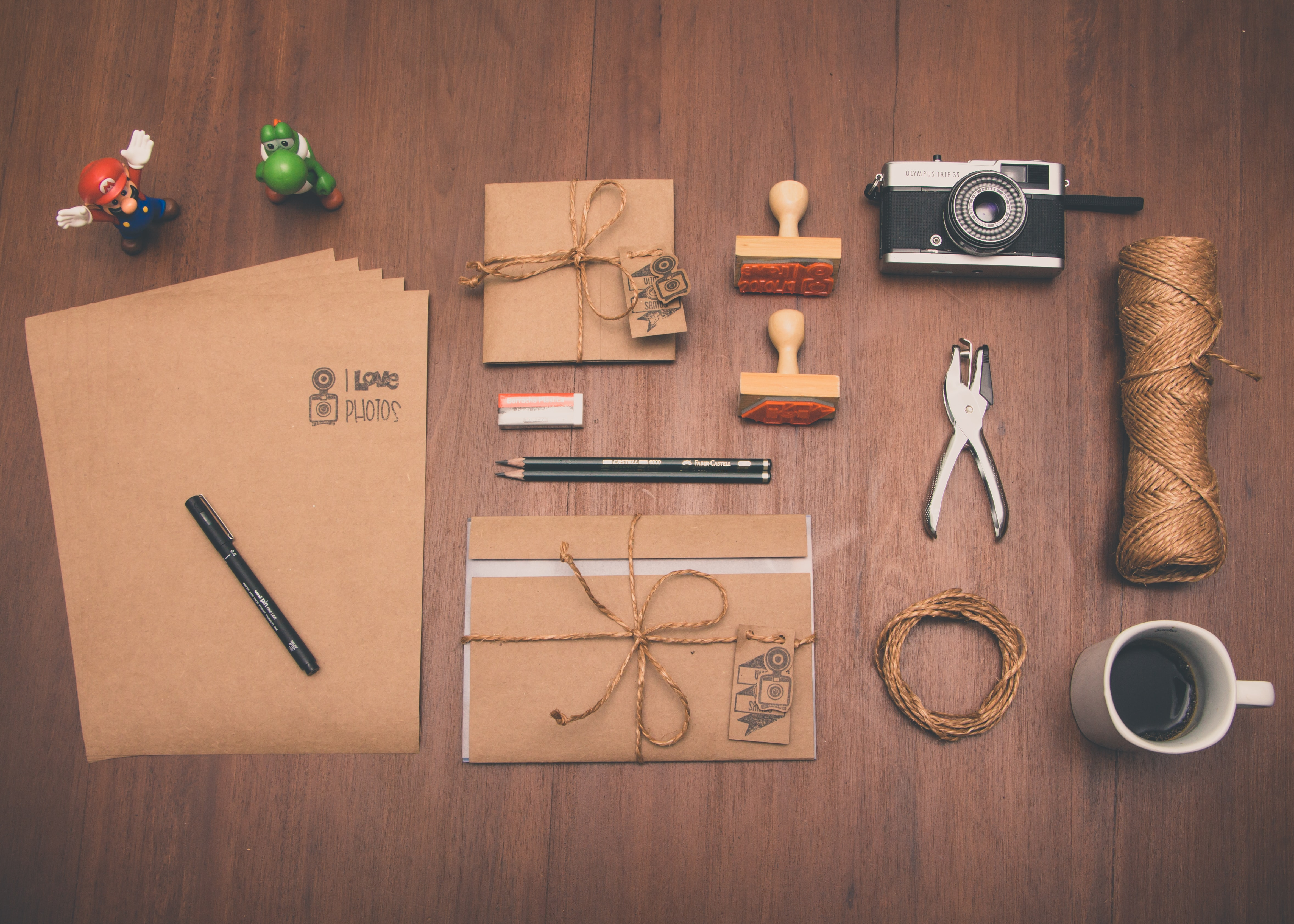 An overhead shot of brown stationery next to a camera, a cup of coffee and colorful figurines