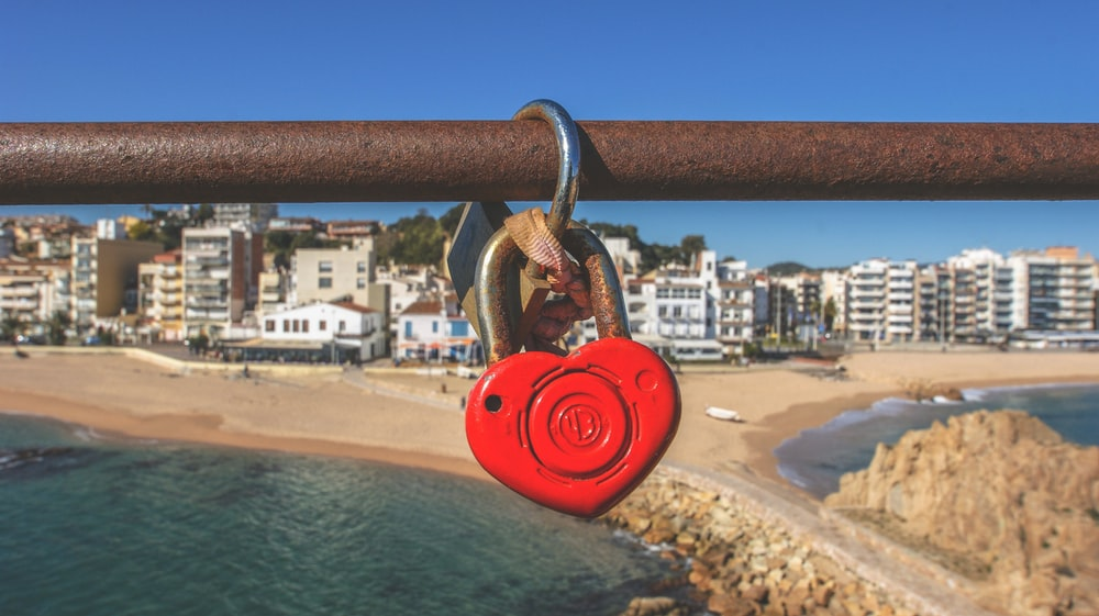 heart padlock hanging on brown pipe