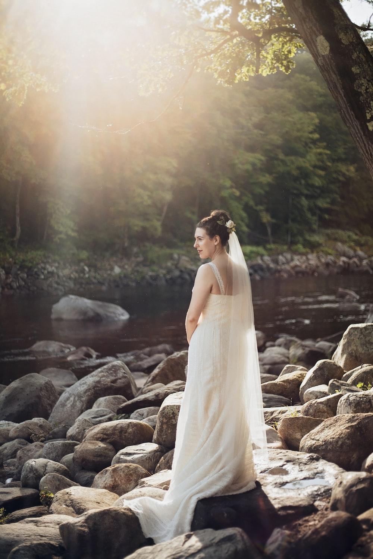 woman standing on gray rock near lake during sunset