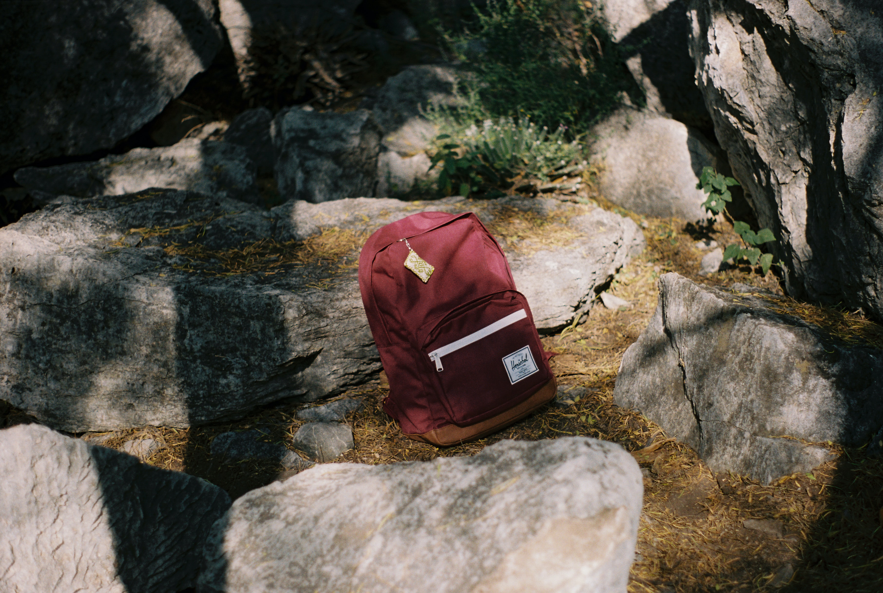 A burgundy Herschel backpack with a coin wallet attached to the zip in the middle of a rocky outdoor area