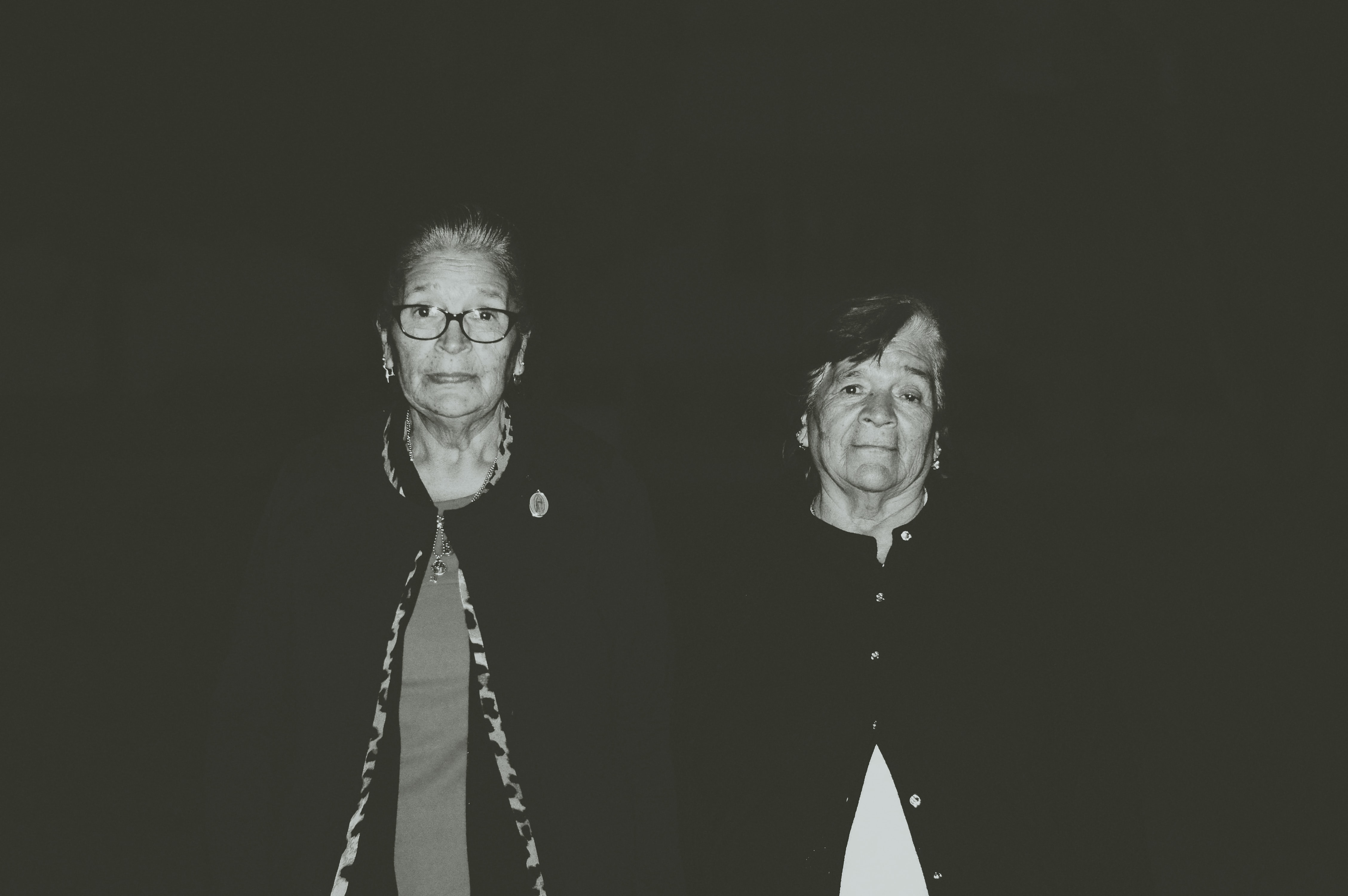 Two older women looking at the camera, with a black background.