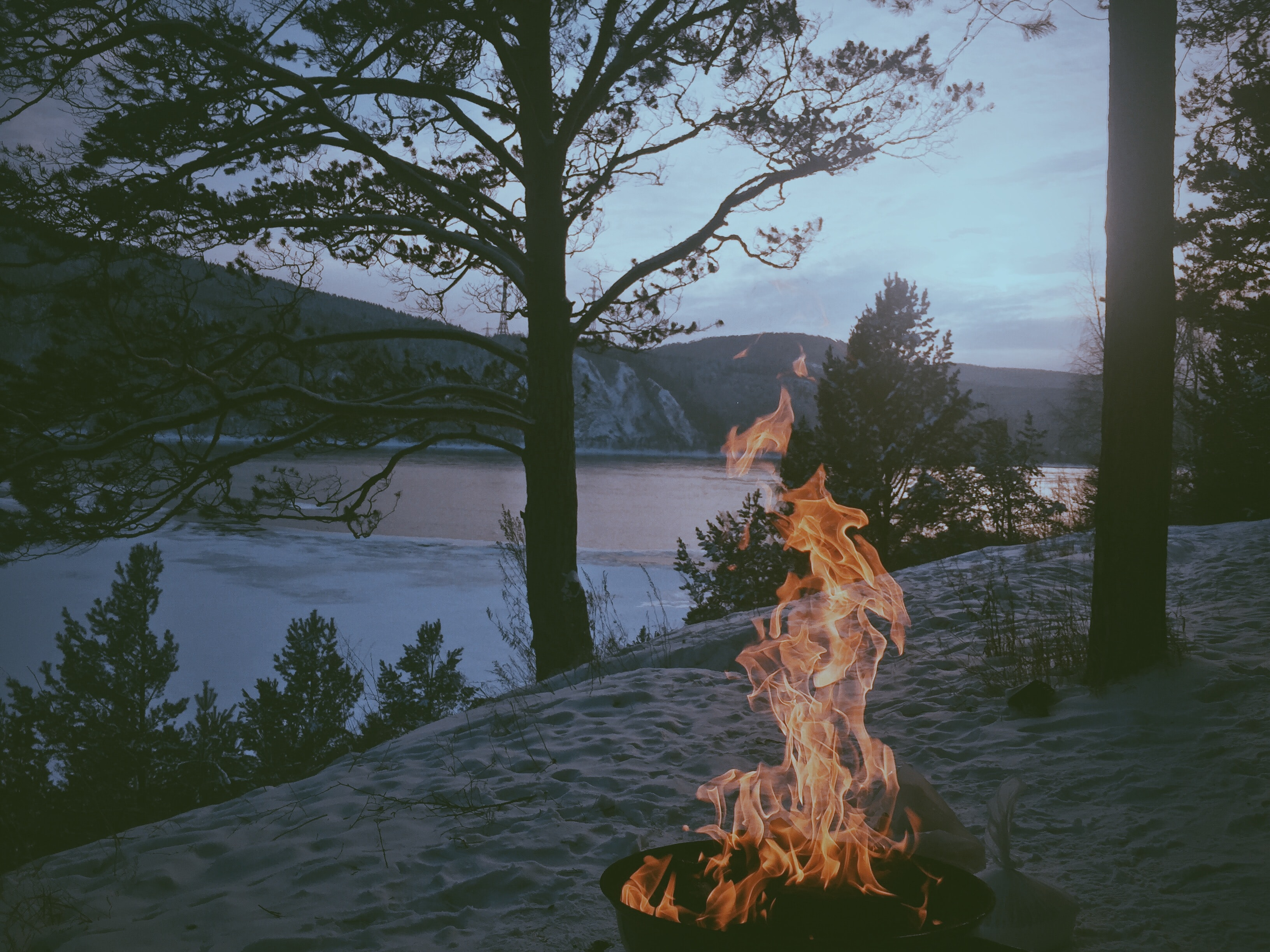 A campfire on a sandy beach near a half-frozen lake