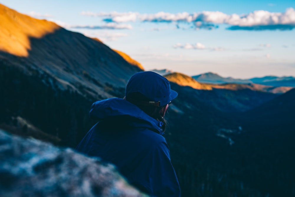 person wearing blue hoodie and blue fitted cap sitting near cliff looking at mountain range under white clouds during daytime
