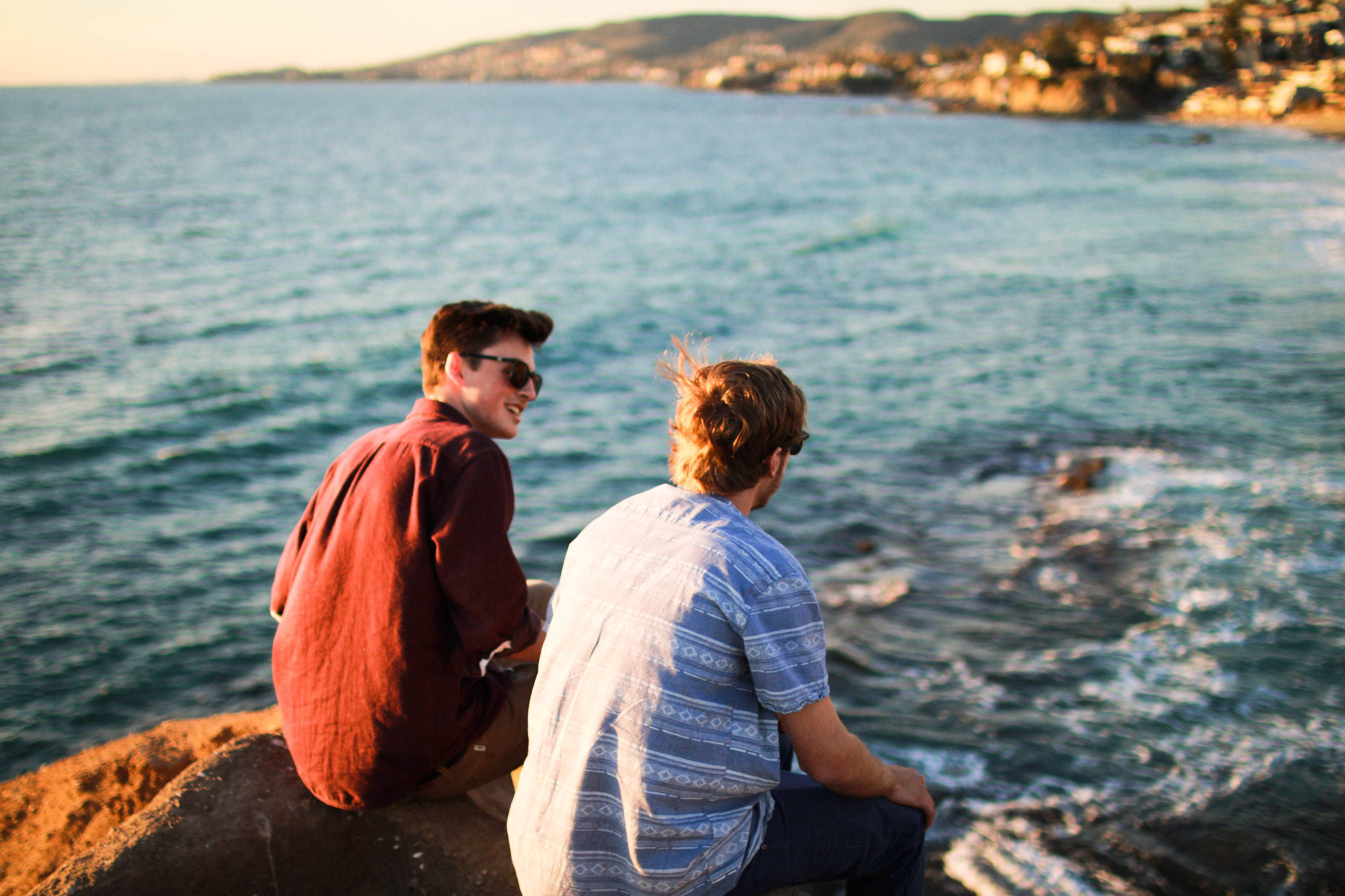 Two guys sitting on a rock and having a conversation by the seashore of Laguna beach
