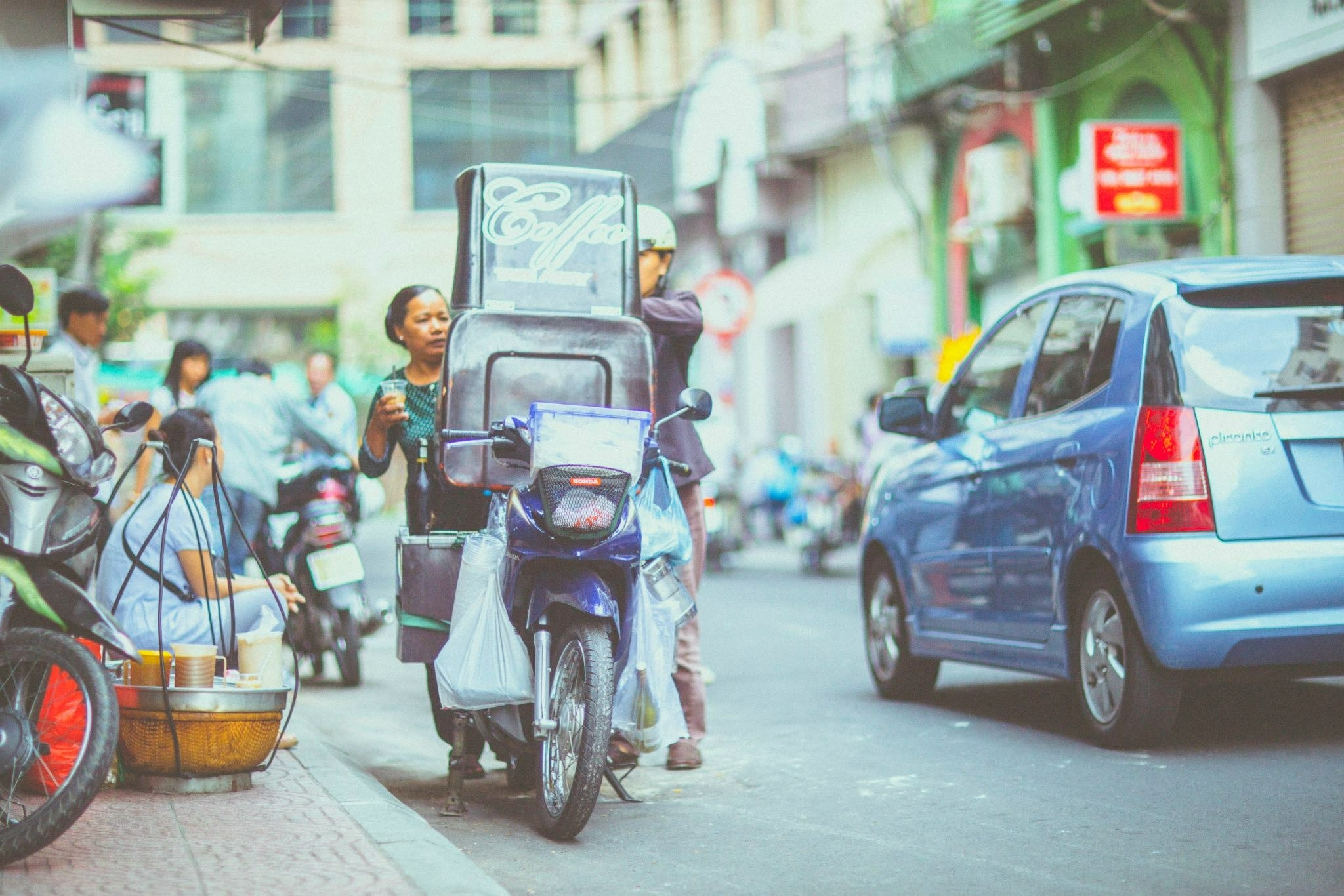 Motorcycle and blue car on city street in Ho Chi Minh City