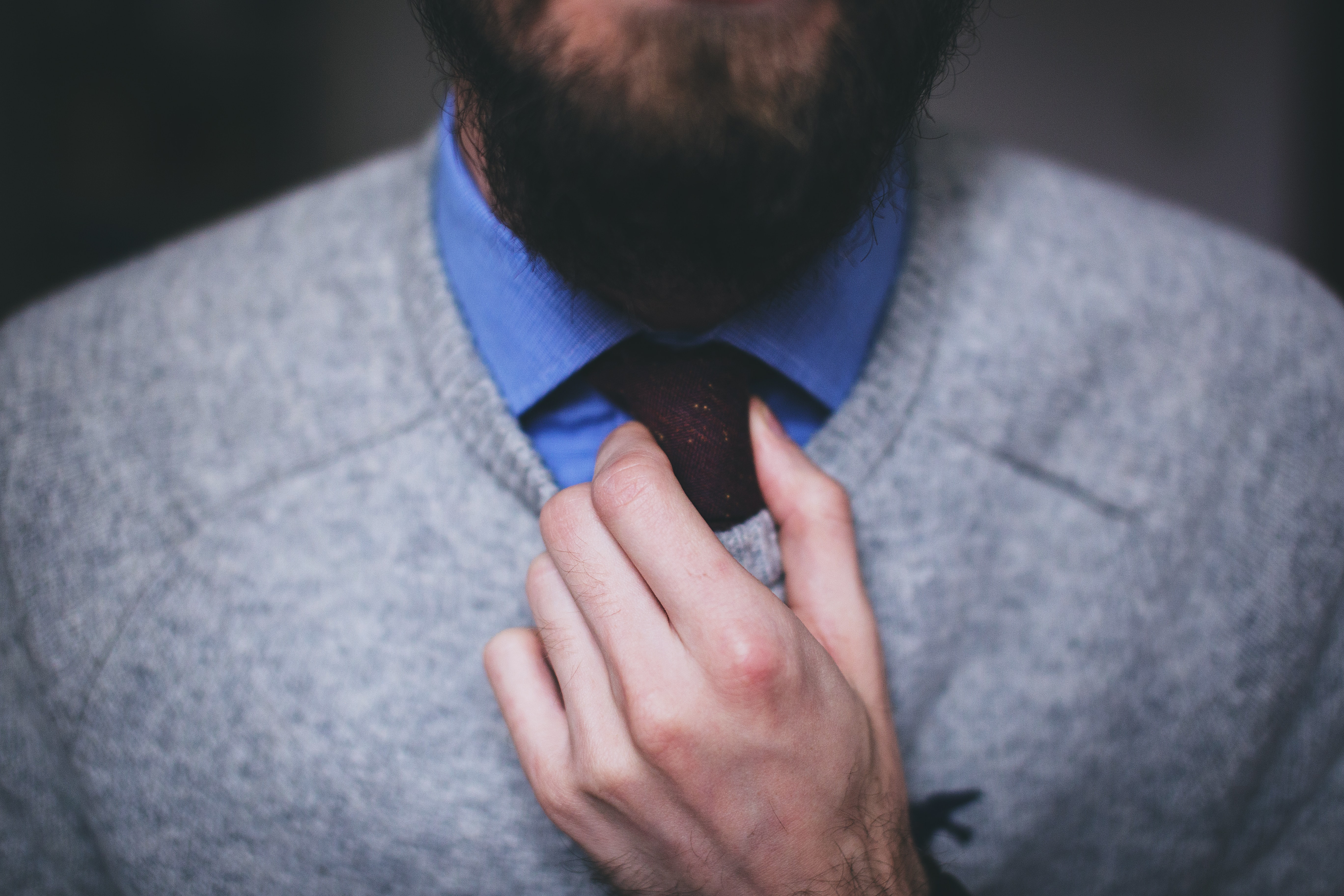 A bearded man in a blue shirt and gray sweater adjusting his tie
