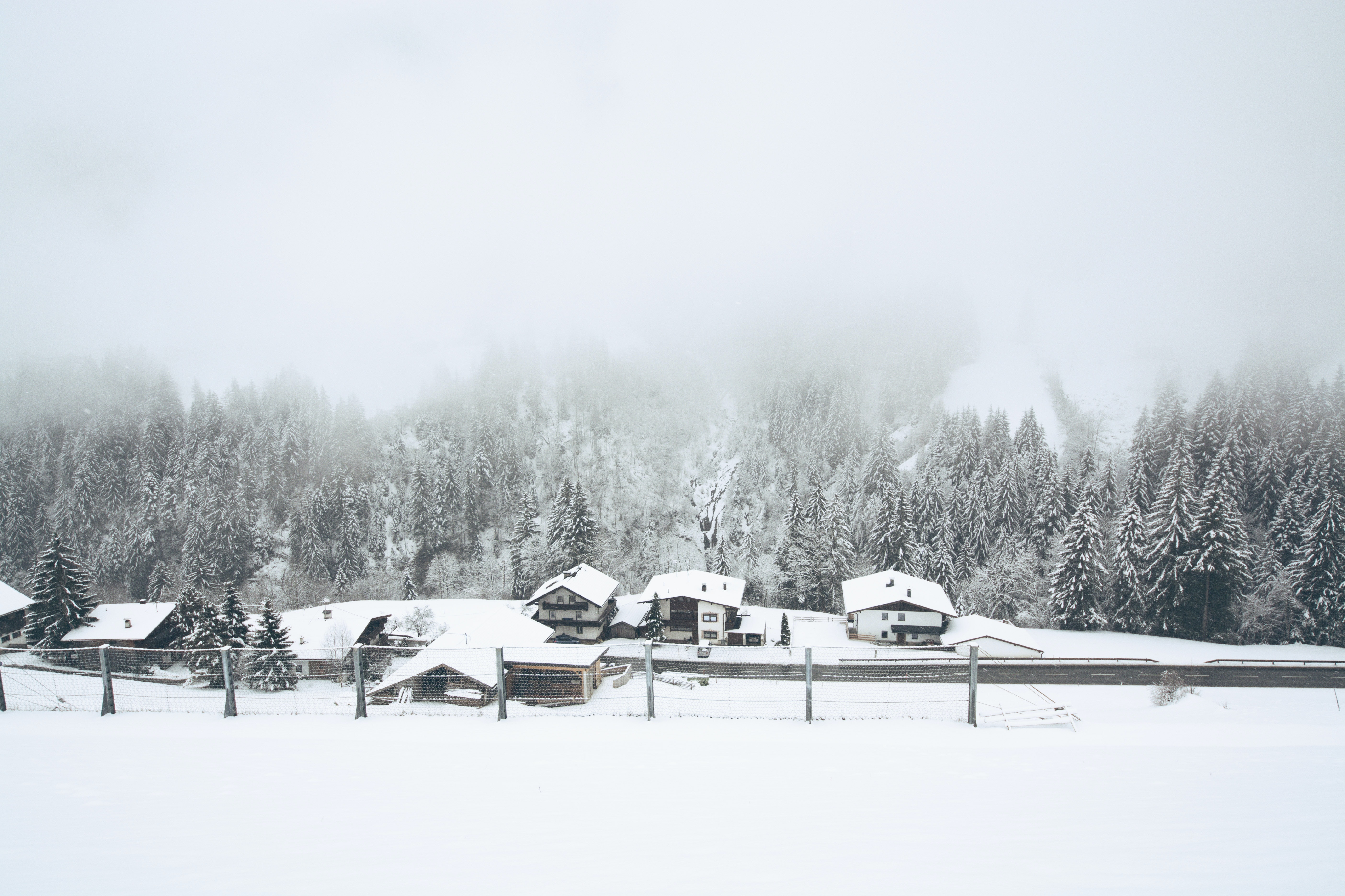 Fog over snow covered cabins near a forest in Finkenberg
