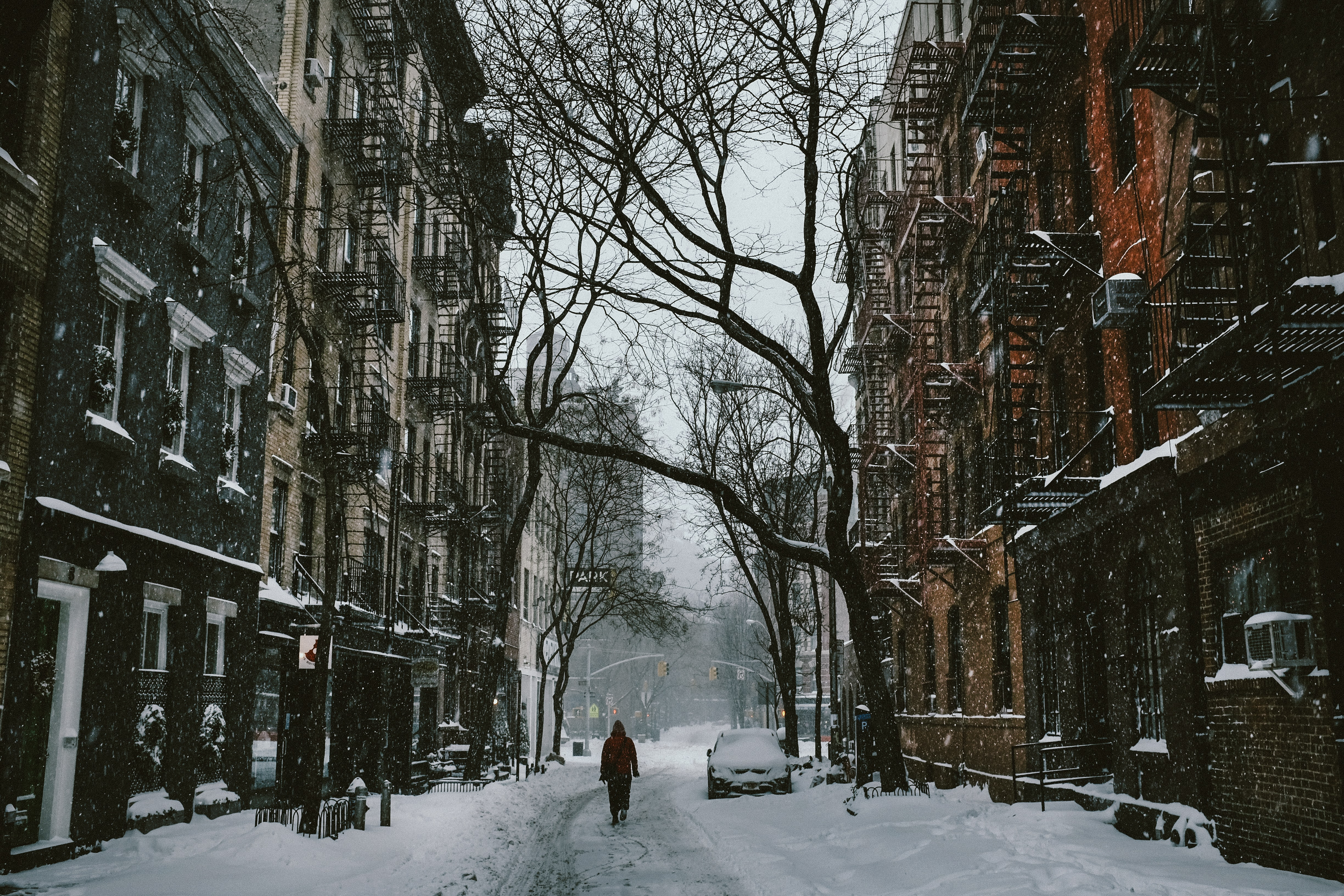A person walking down the snow covered street surrounded by houses and trees in the city.