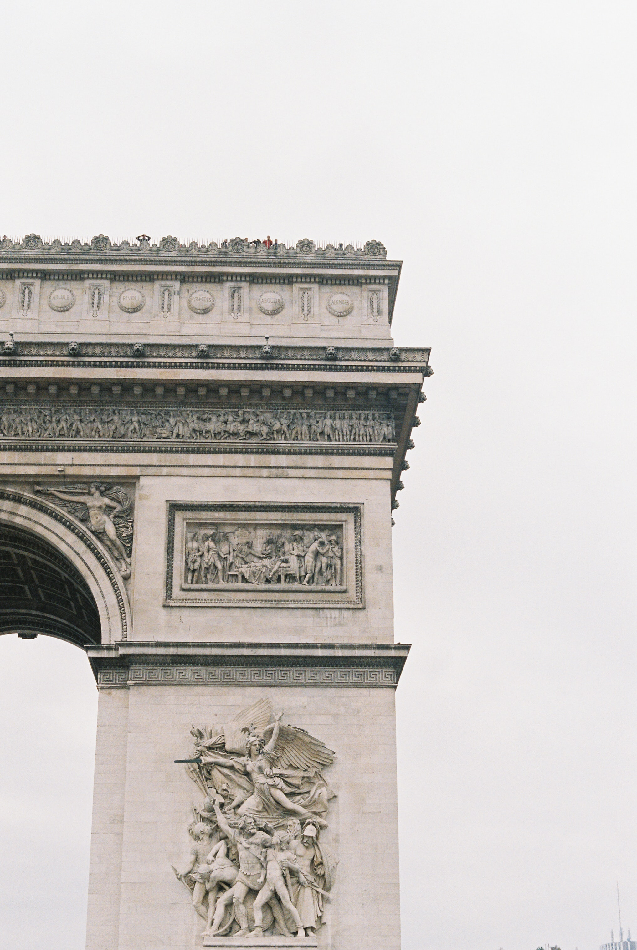 The stone archway of the Arc De Triomphe in Paris, France with memorial statues.