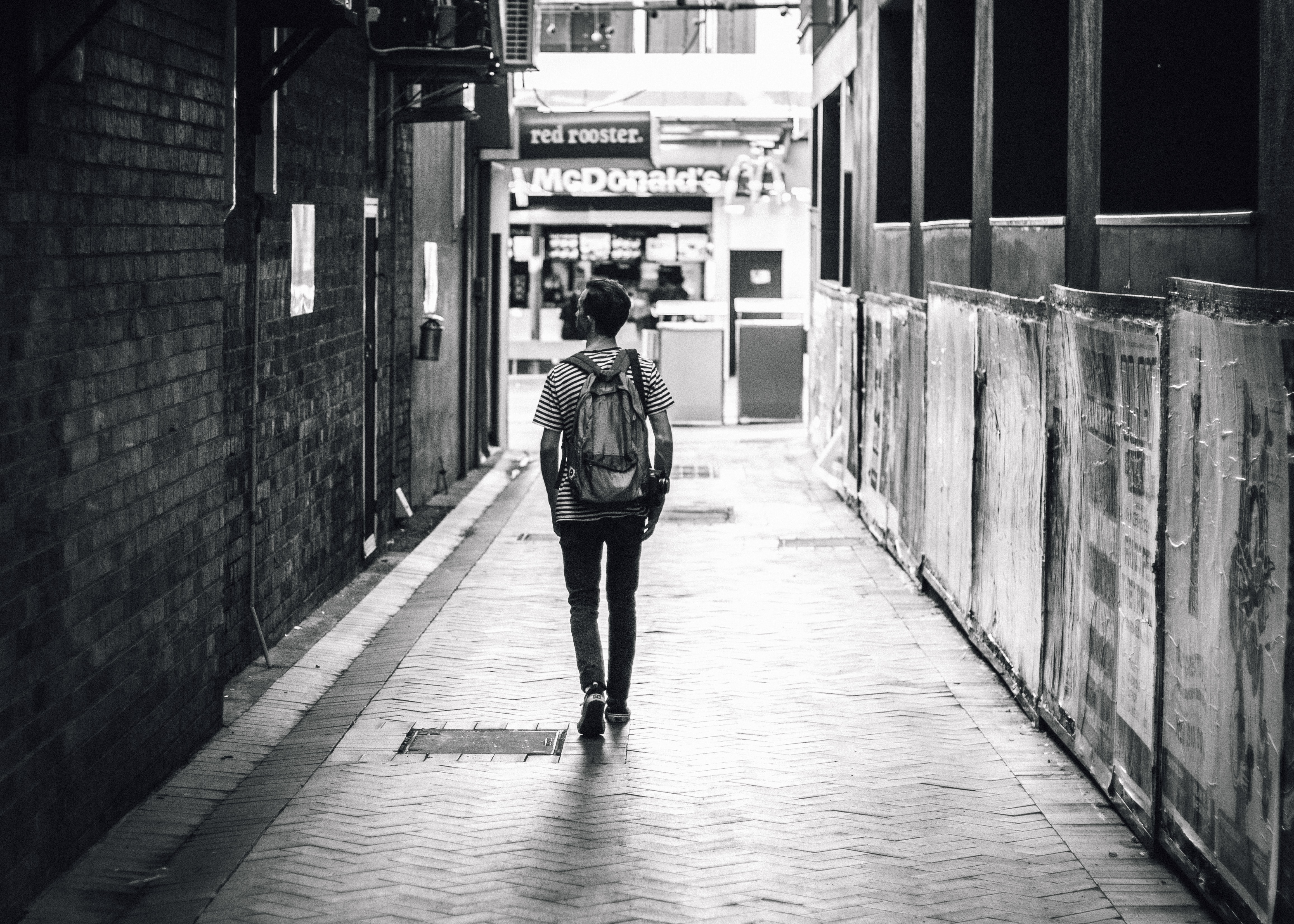 Man walking down an open alley in a striped shirt with a McDonald's ahead of him