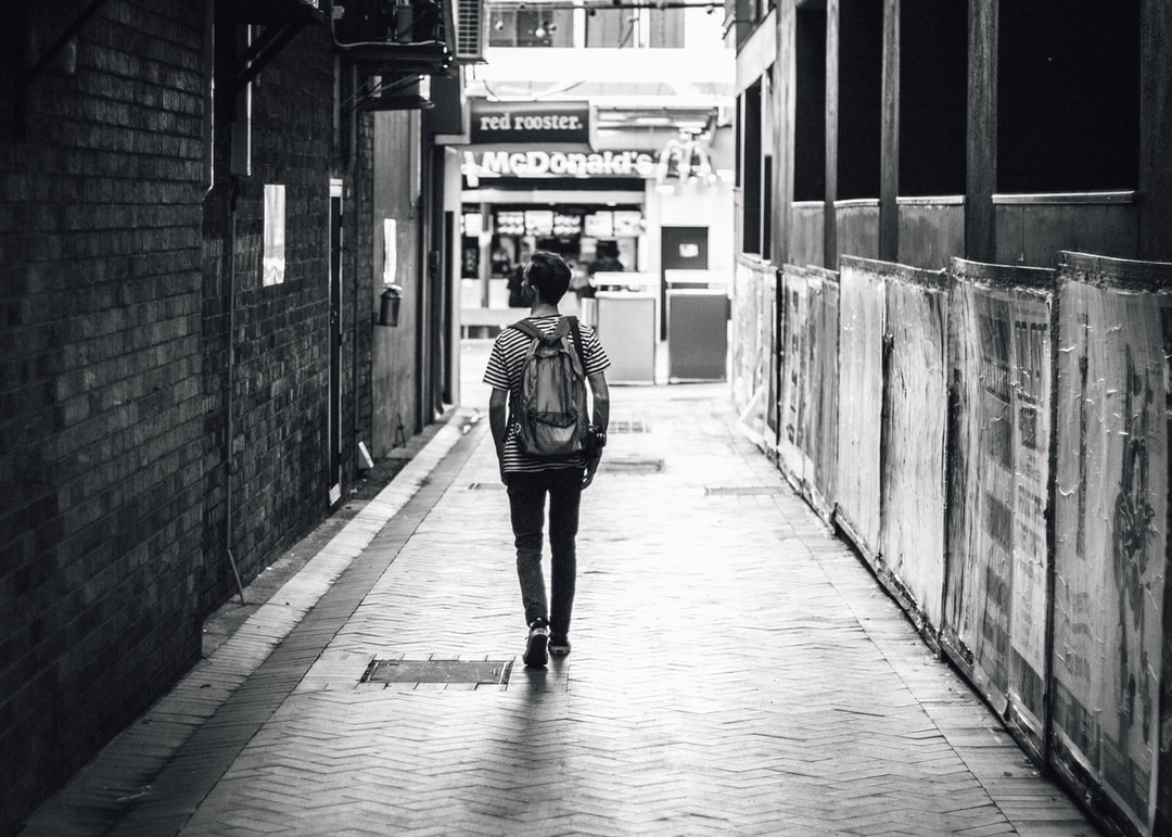 man walking between concrete buildings
