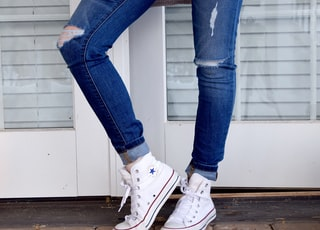 women's distressed blue denim jeans and pair of white Converse Allstar high-tops