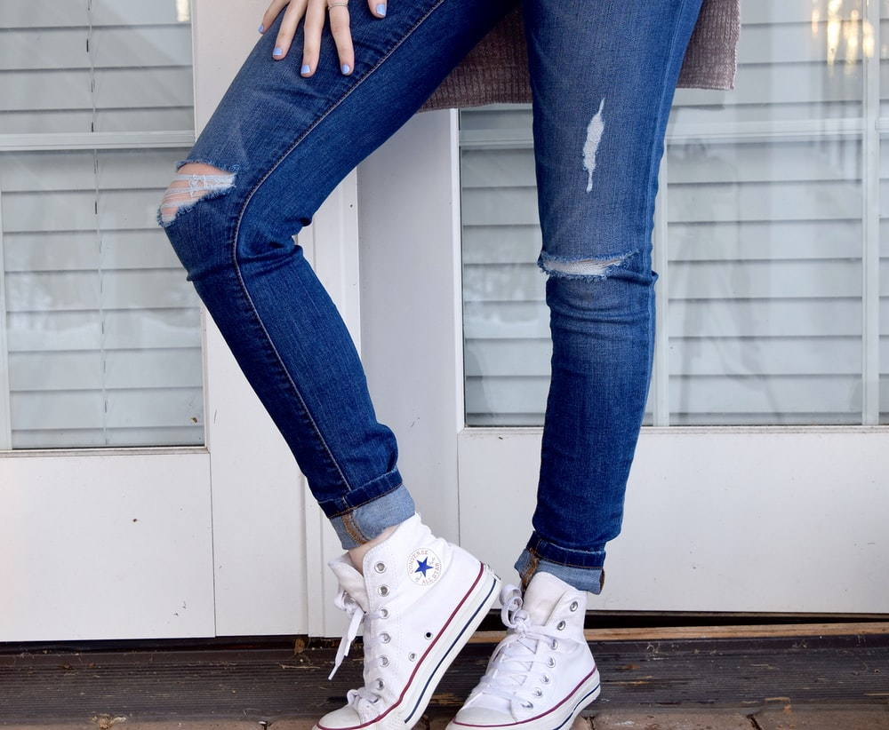 1b7ea510f6b3 women s distressed blue denim jeans and pair of white Converse Allstar high- tops