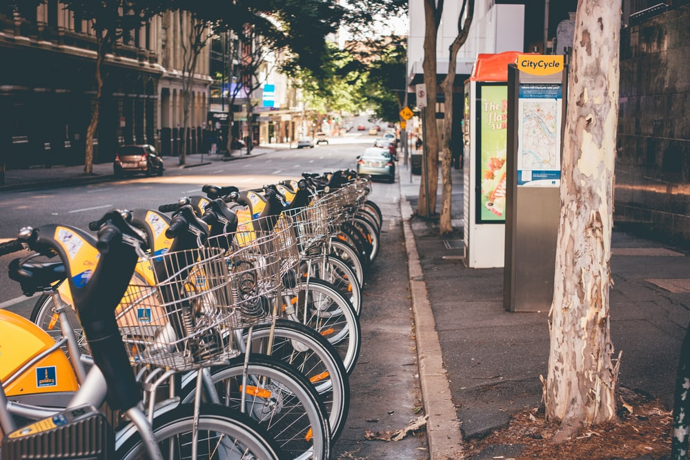 assorted commuter bicycle park ahead near yellow car at daytime