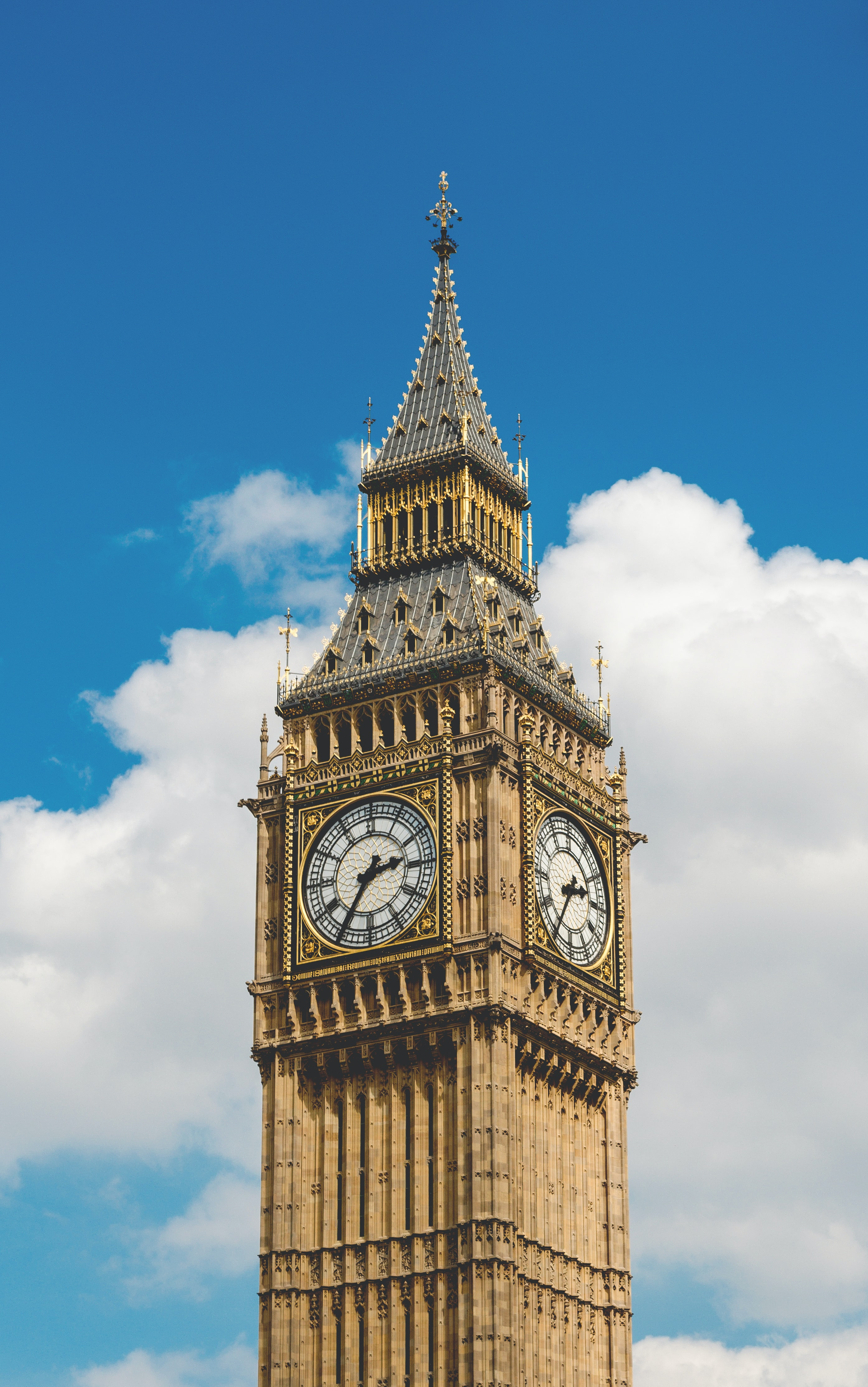The Elizabeth Tower housing the Big Ben bell against a fluffy cloud in a blue sky