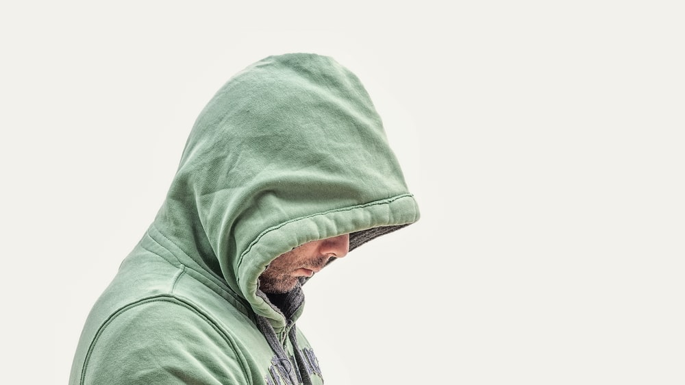man wearing green hooded jacket with white background