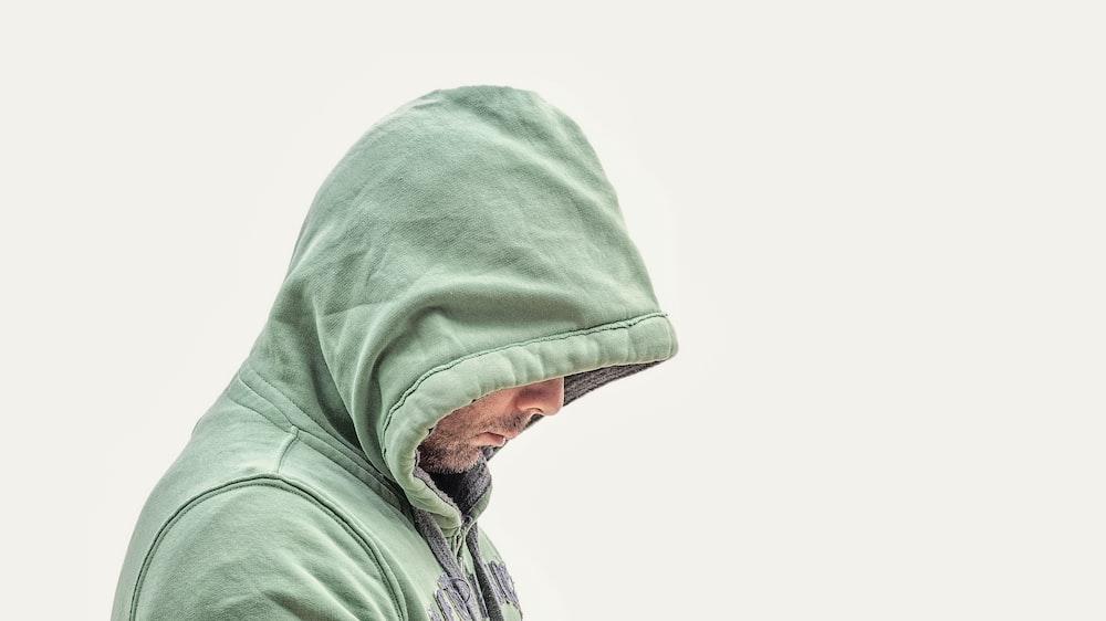 白い背景の緑のフード付きジャケットを着た男