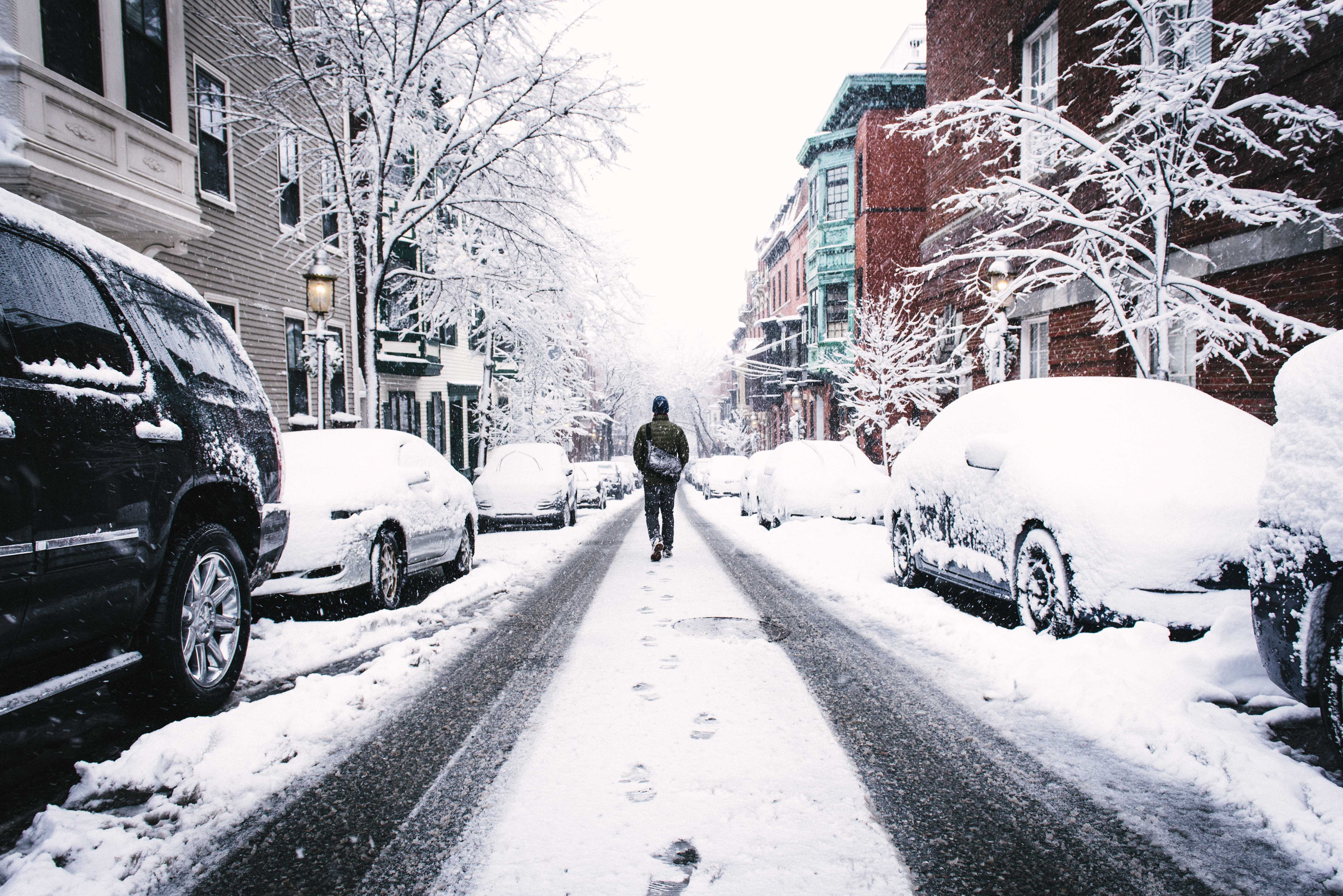 A pedestrian walks between parked cars on road that is covered in snow