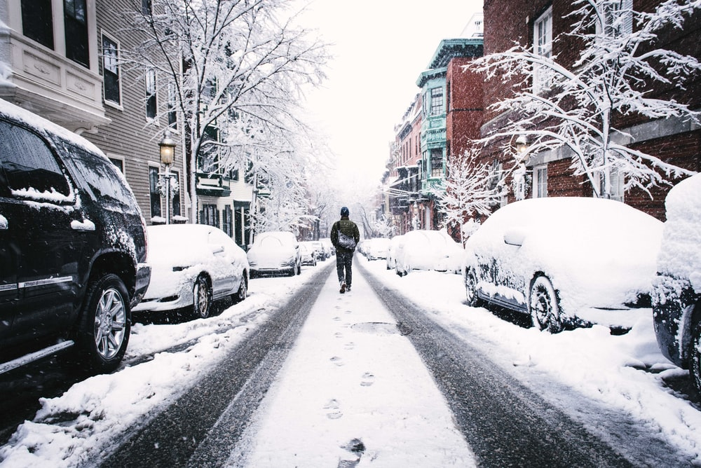 man walking on road covered with snow between vehicles and concrete buildings during daytime