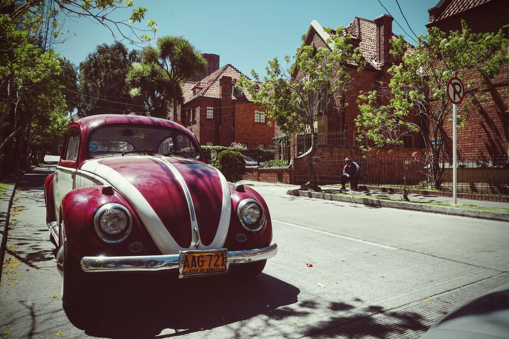 red and white Volkswagen Beetle on road near brown house