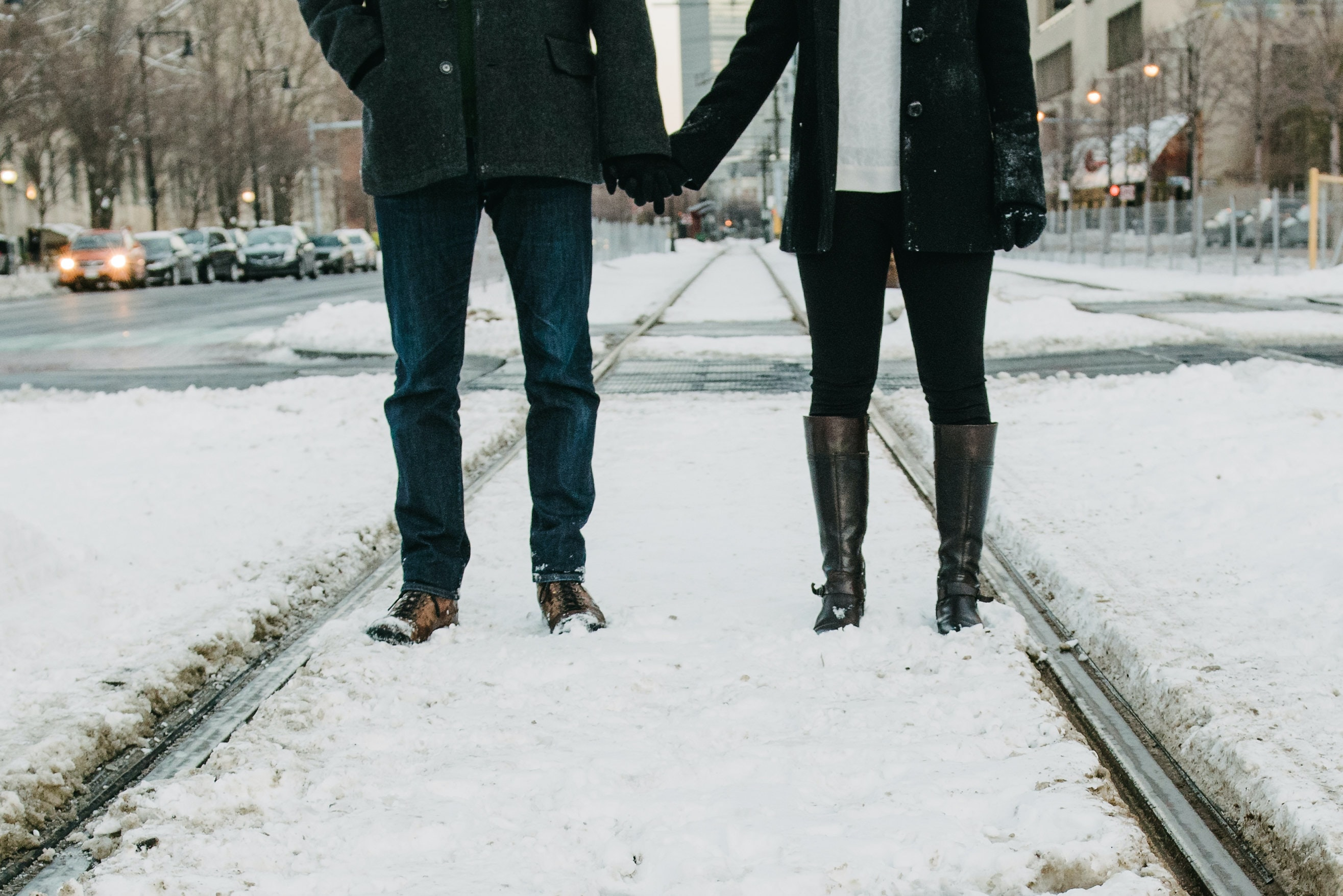 On train tracks covered in snow, two lovers stand holding hands