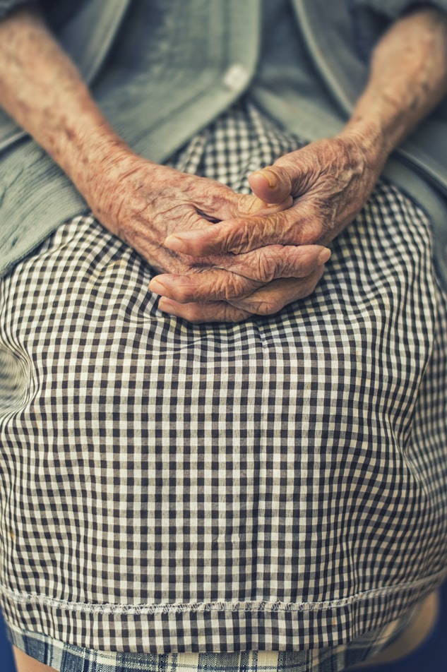 Elderly person with hands crossed on lap