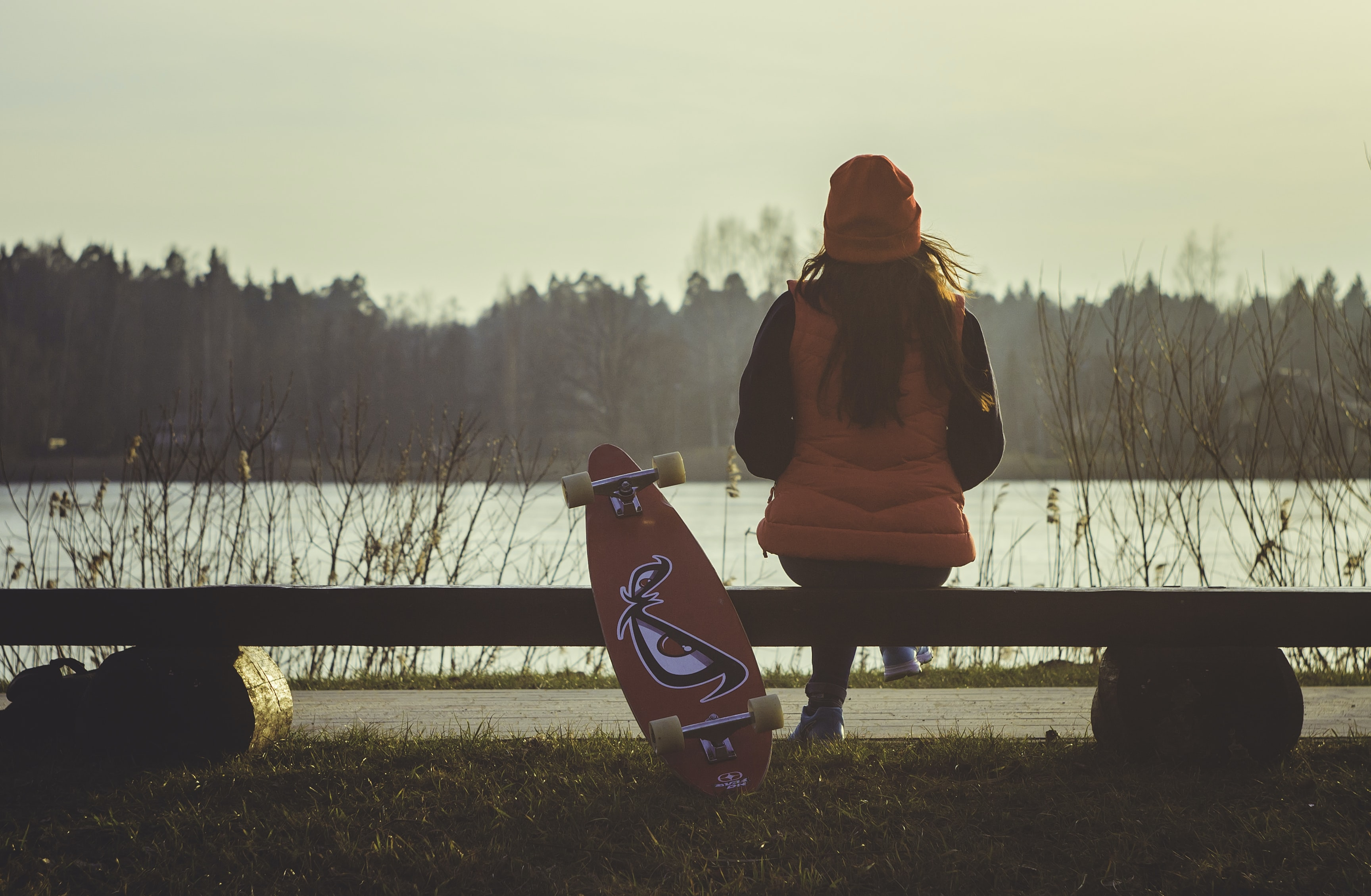 Woman in orange with a long board sitting on a lake bench