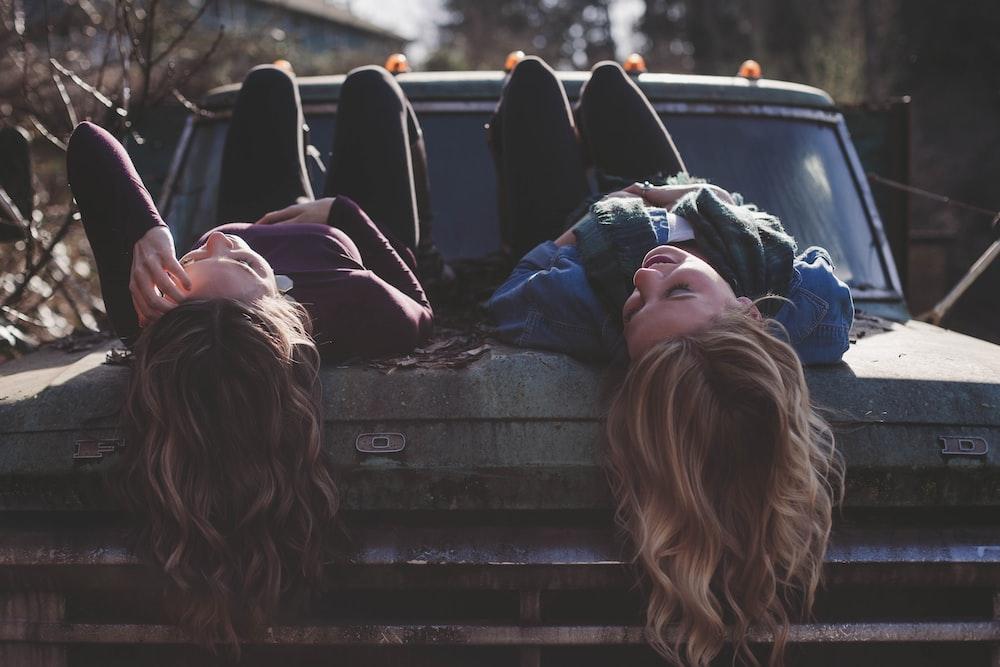 two women lying down on vehicle