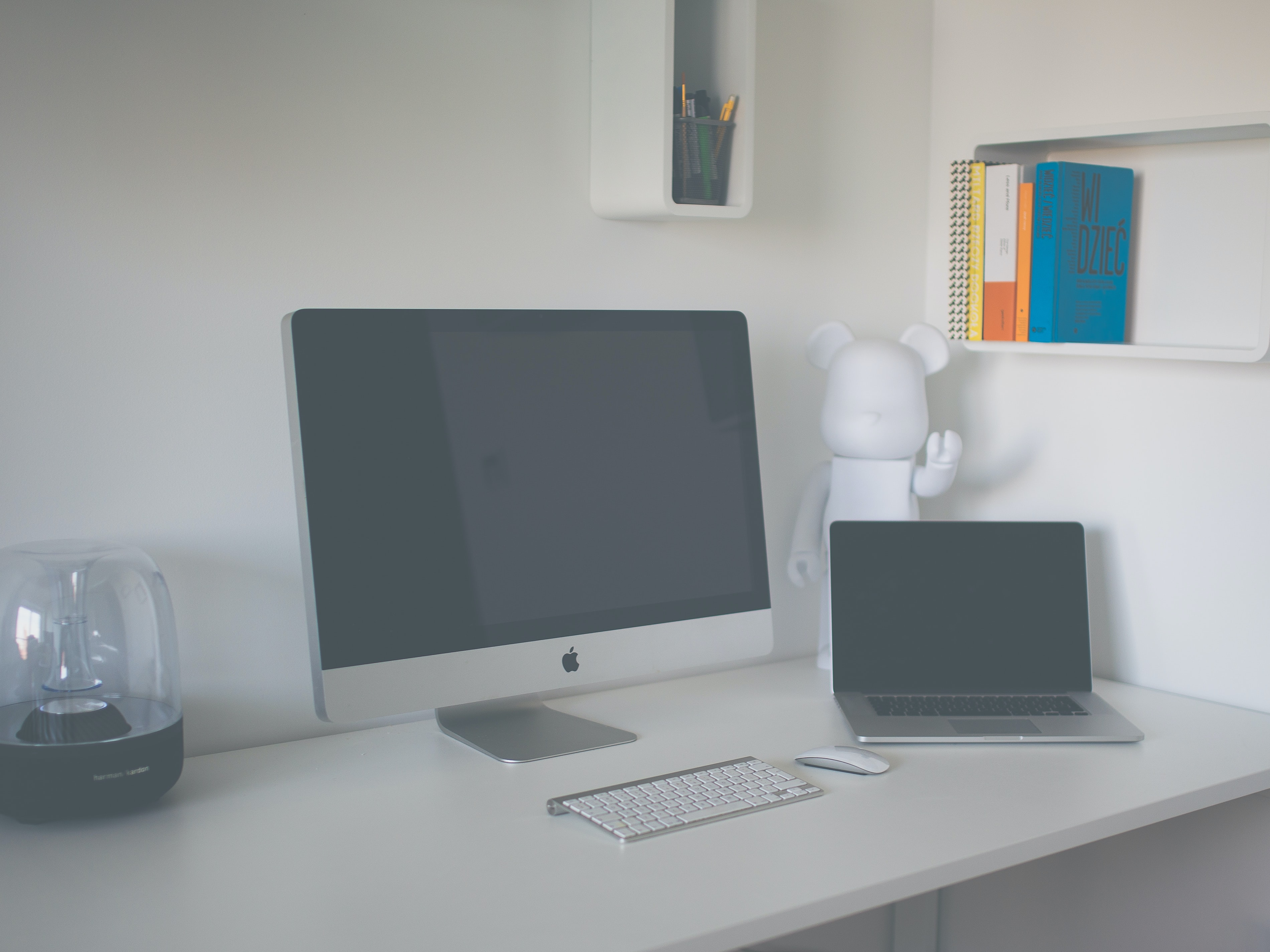 A clean white workspace with an iMac, a Macbook and a bookshelf