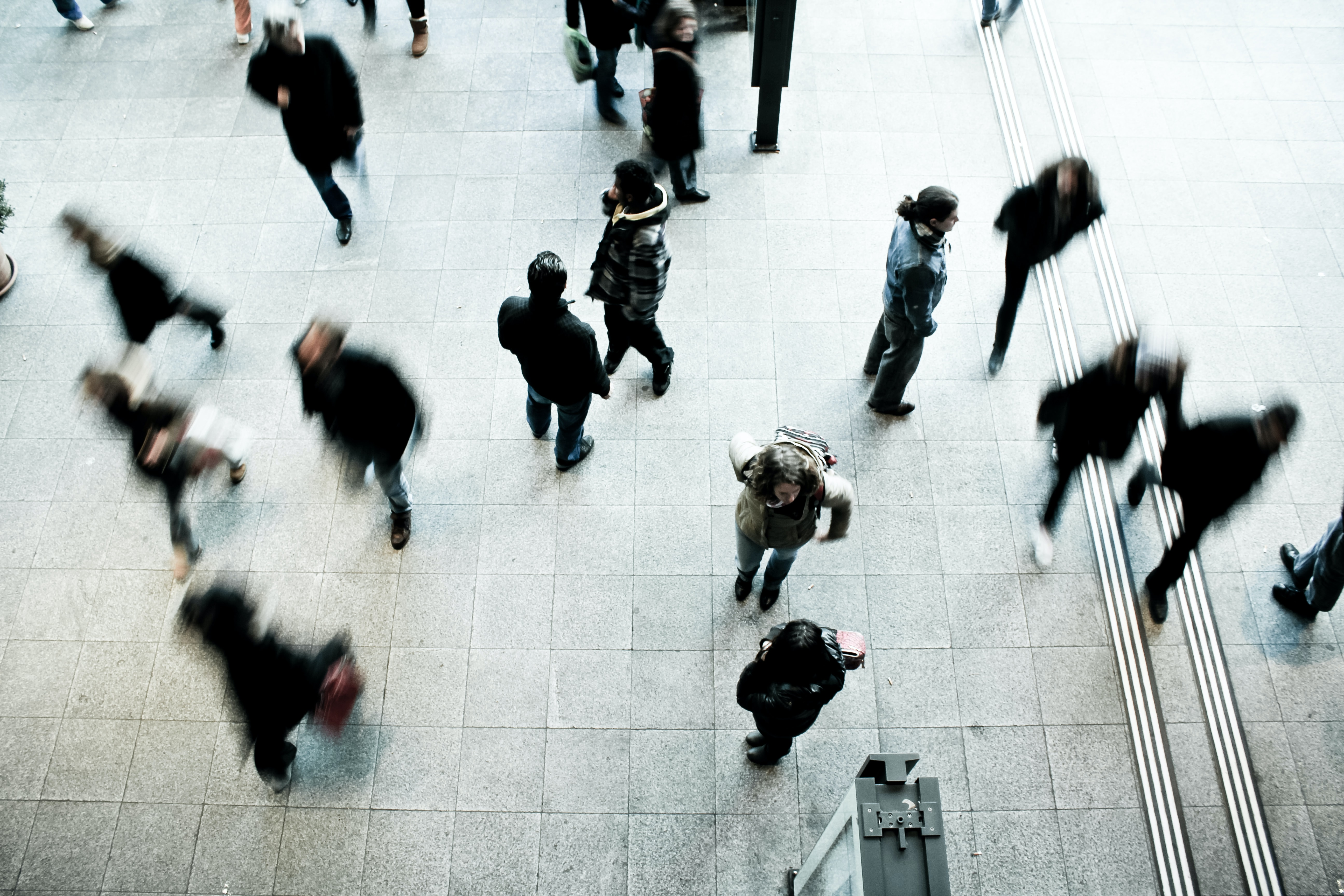 An overhead shot of people walking across a railway station