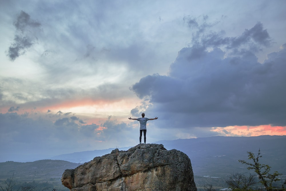 man standing on top of rock mountain during golden hour