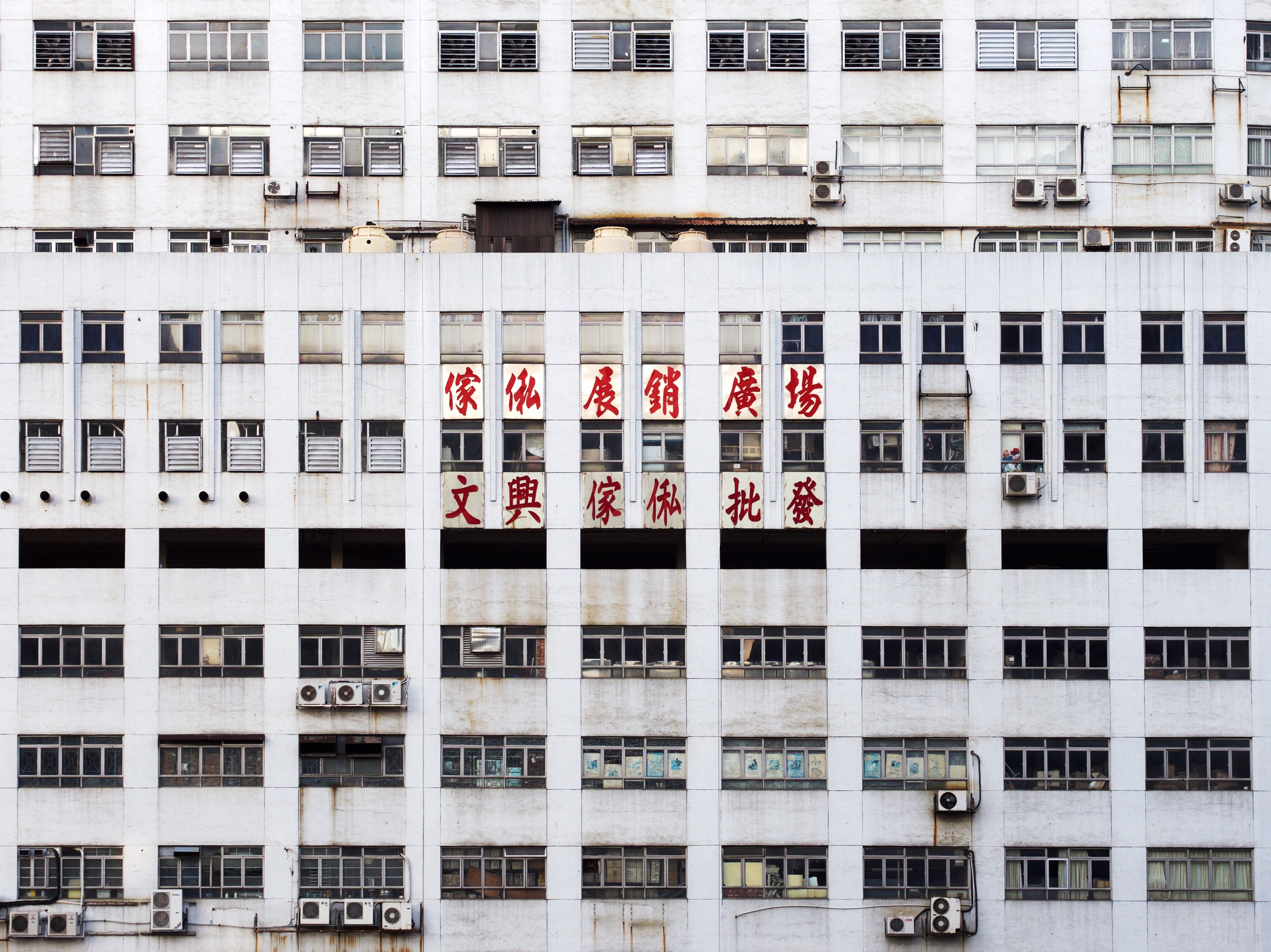 gray multistory building with red Oriental script signage