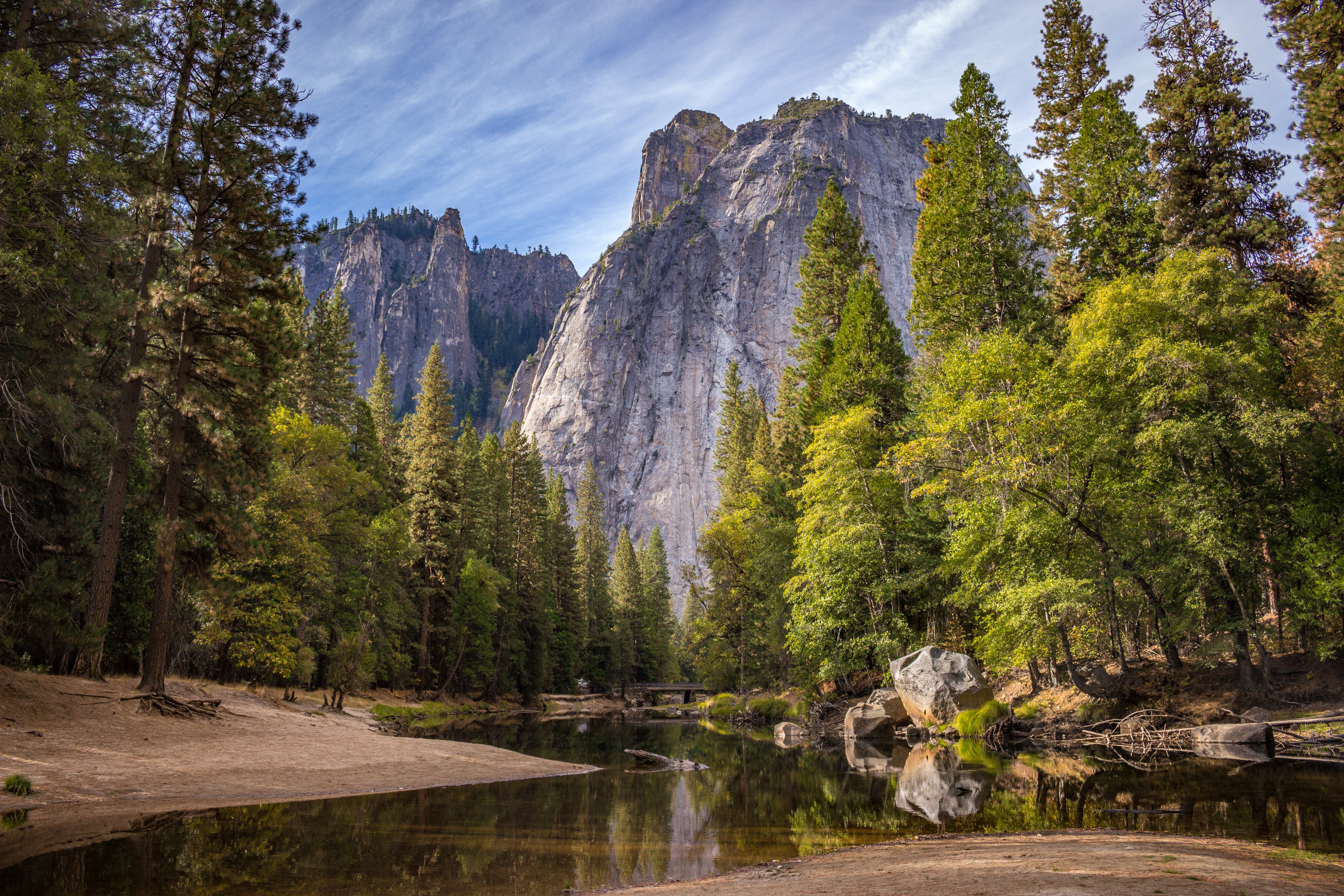 Tall cliffs in Yosemite National Park towering above a small river