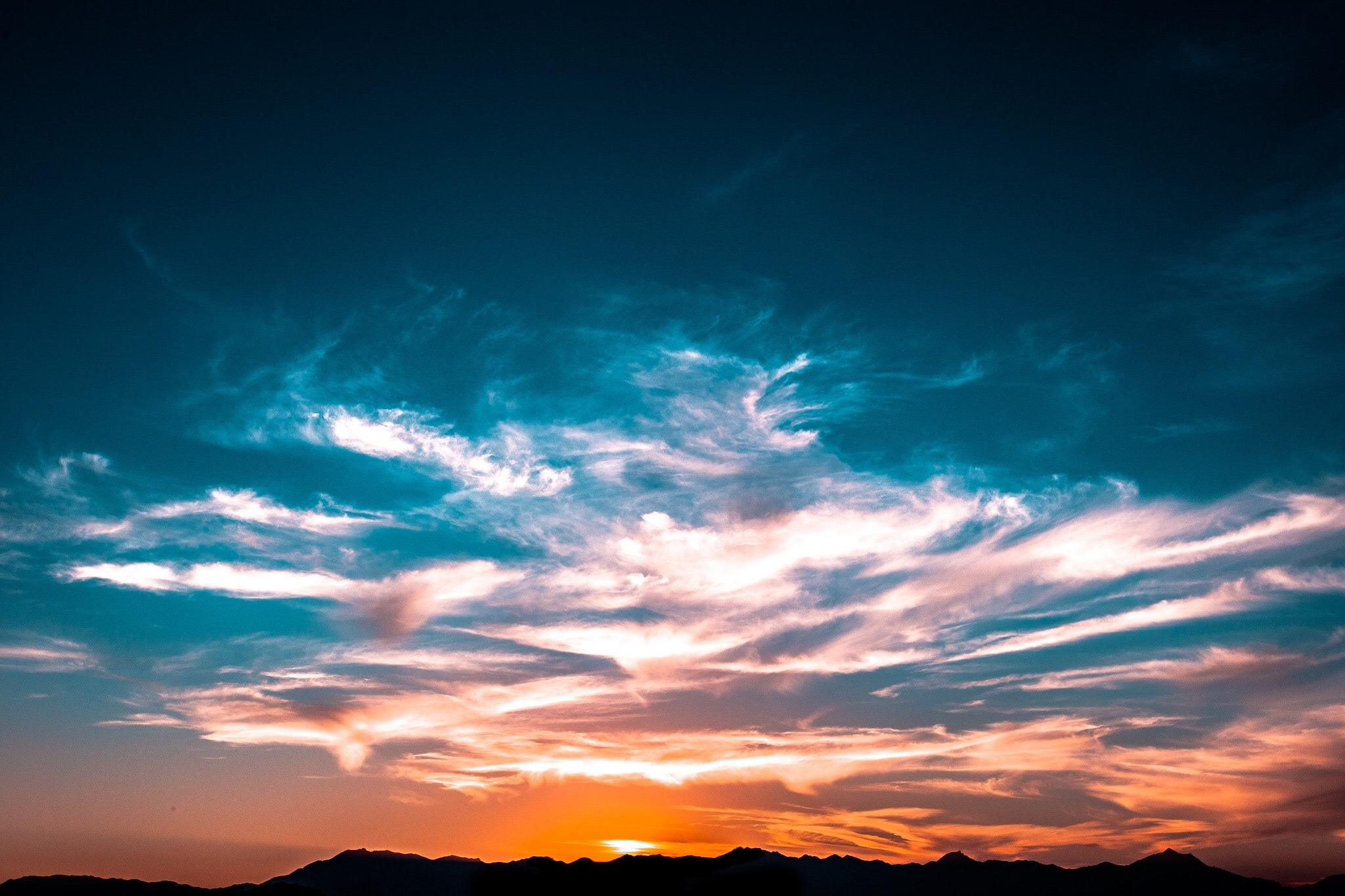 Wispy clouds against the illuminated orange and blue sky with the sun behind the hills.