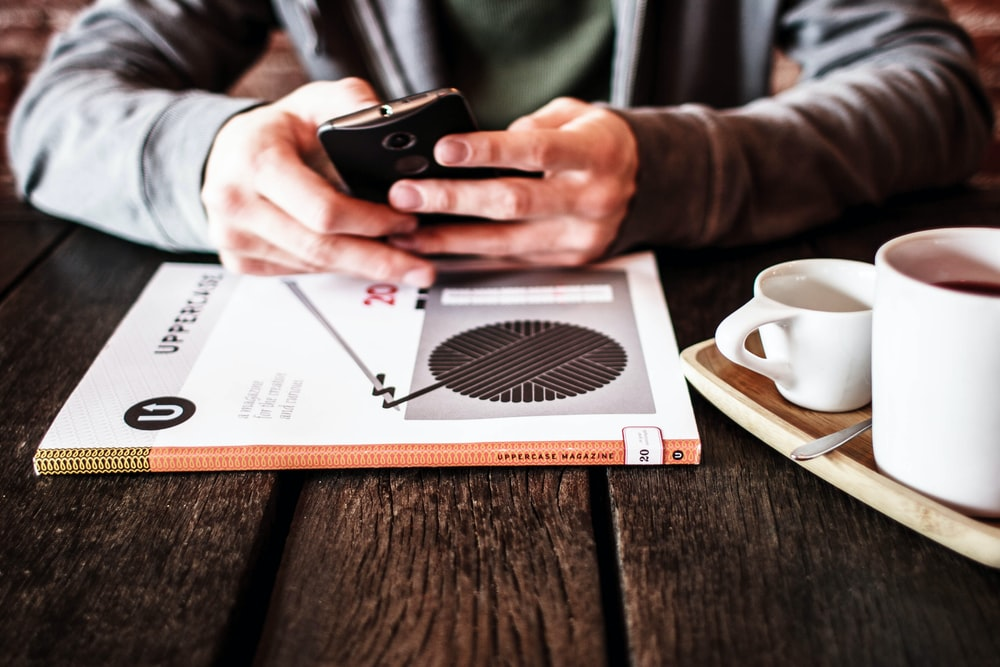 A person in a hoodie using a phone at a table over coffee