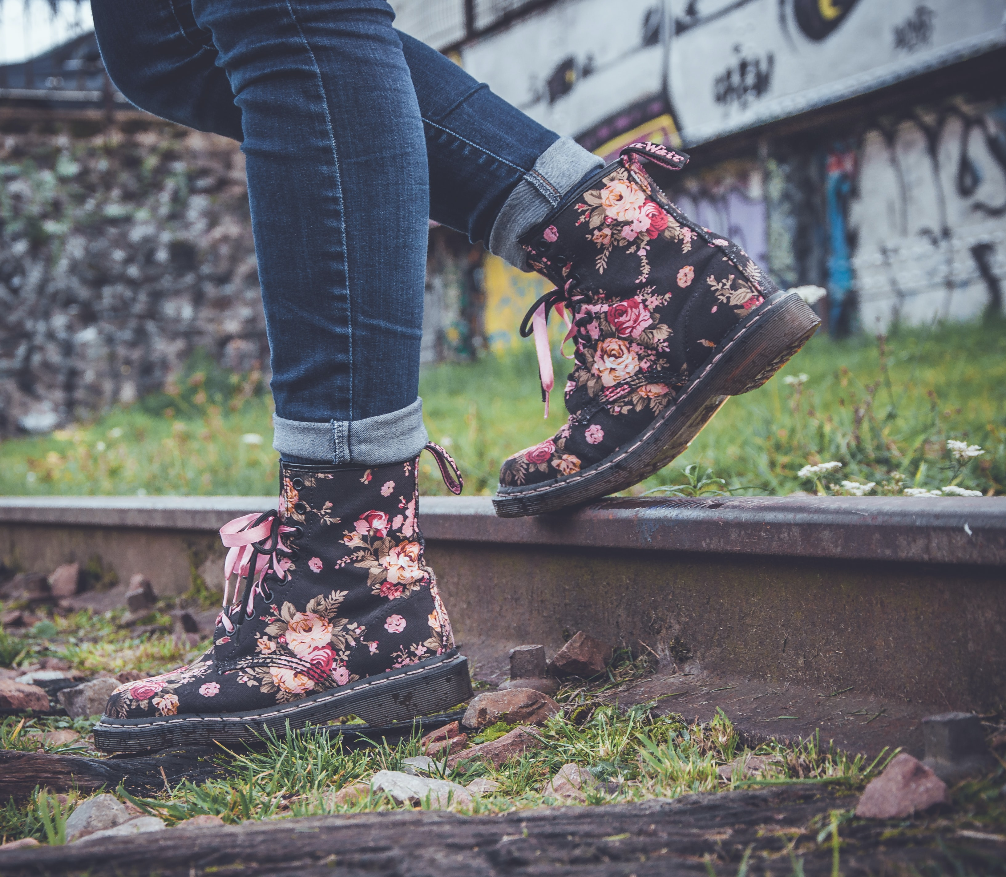 A close-up shot of a person wearing floral boots stepping on a railway track with graffiti behind
