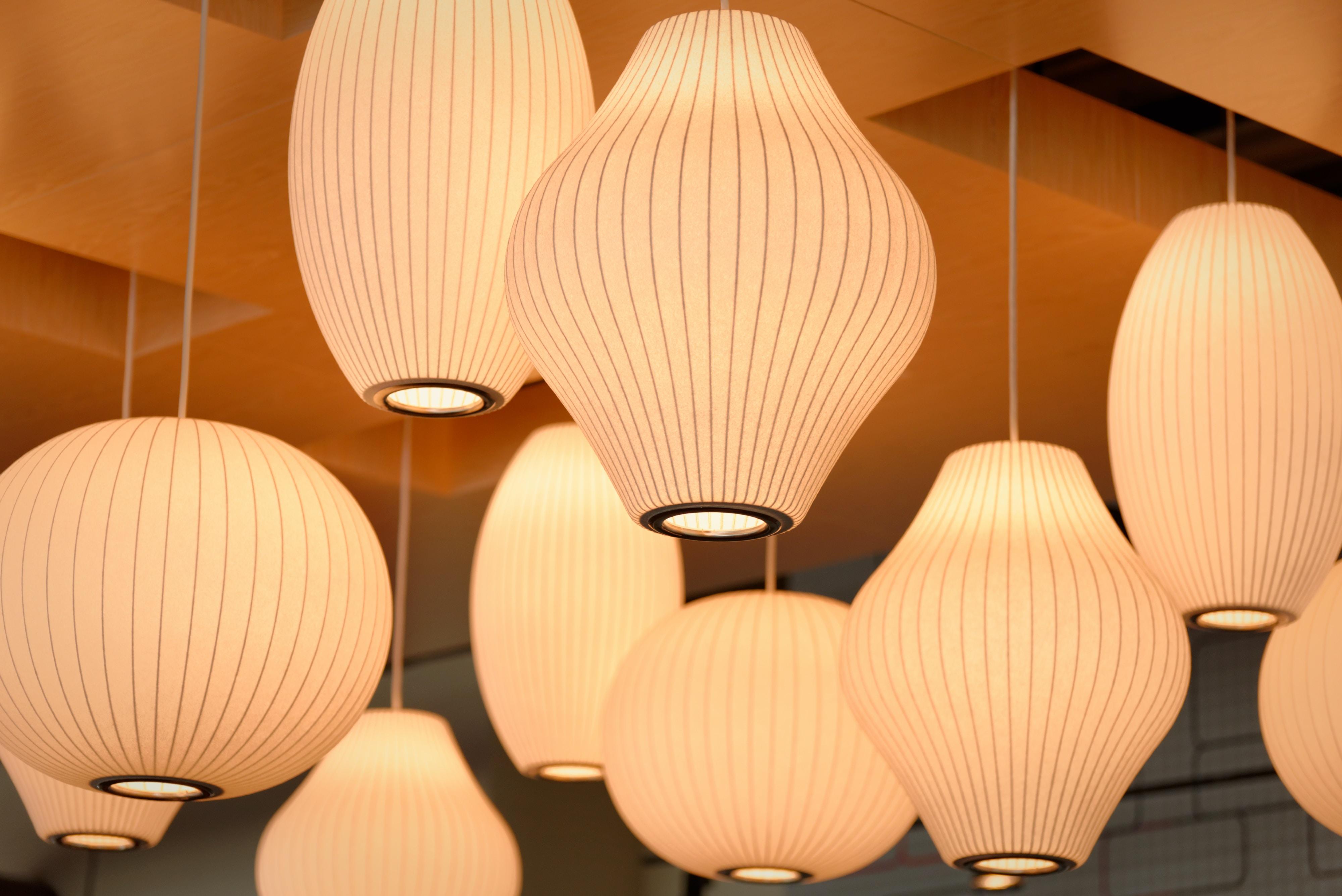 Multiple lanterns hanging from an orange ceiling