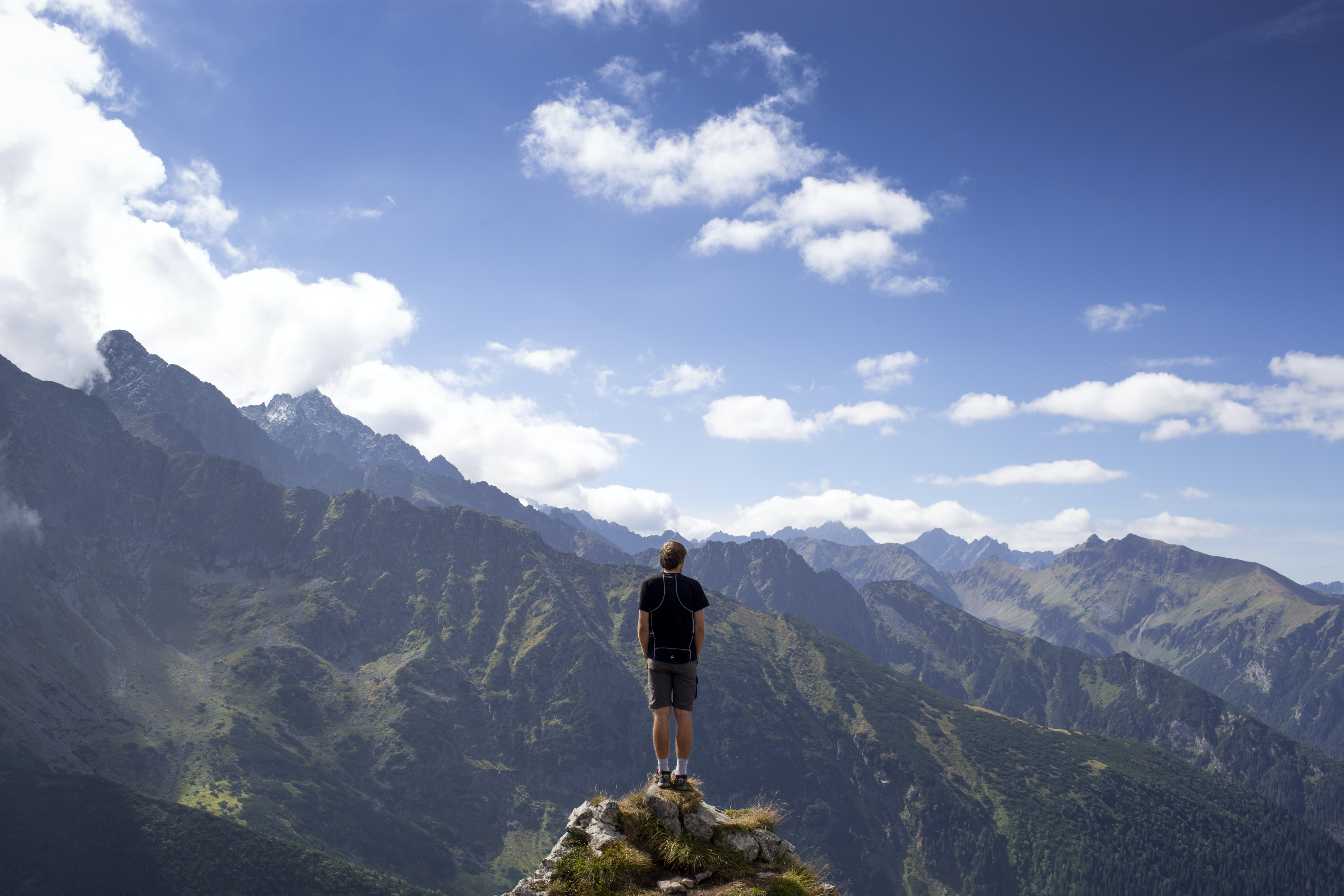 man wearing black shirt and gray shorts on mountain hill beside mountains under white and blue cloudy skies