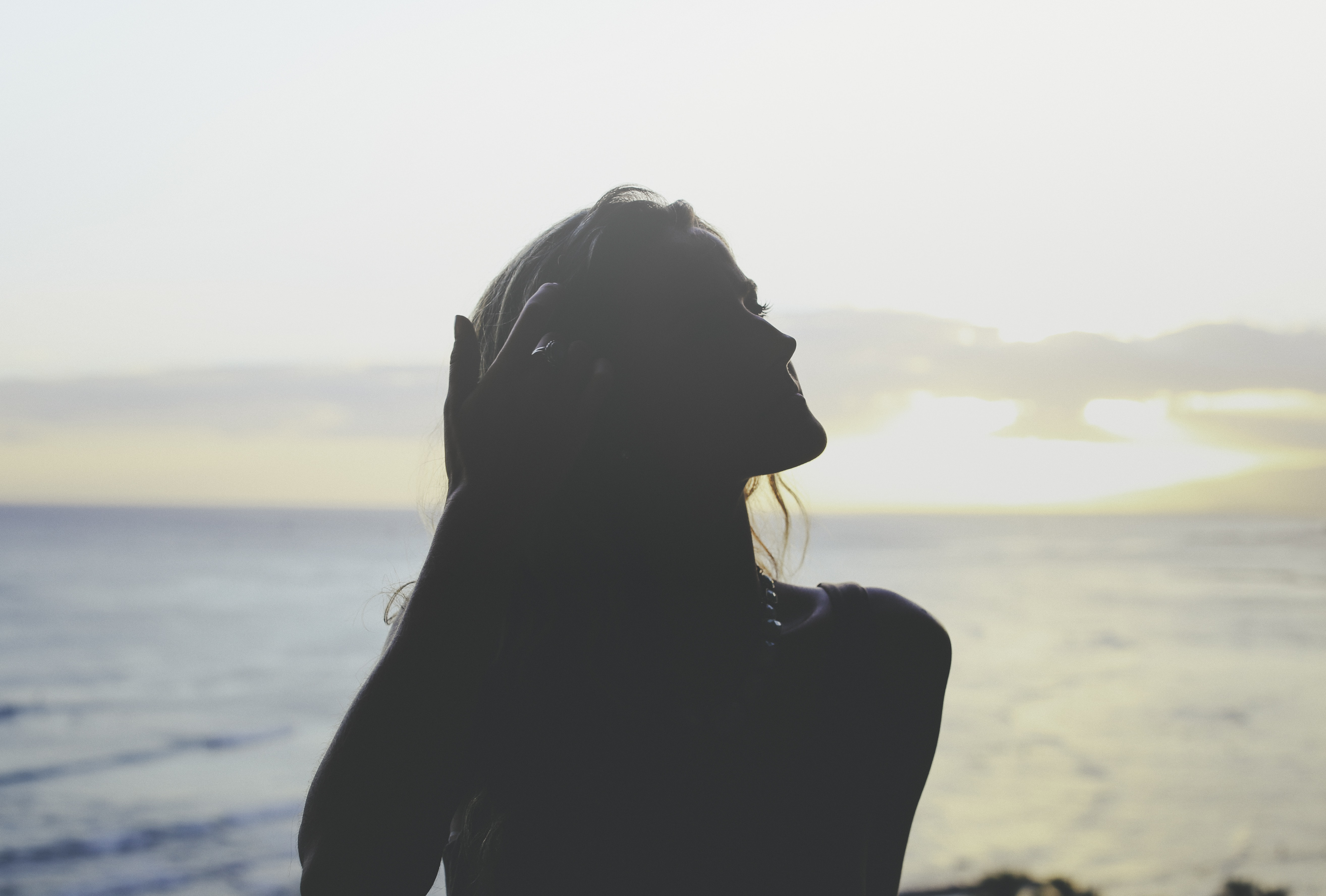Silhouette of a woman standing in the shadows near the ocean at sunset