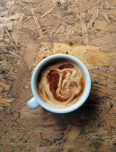 A vertical high angle closeup shot of espresso coffee in a white ceramic coffee cup on wooden surface