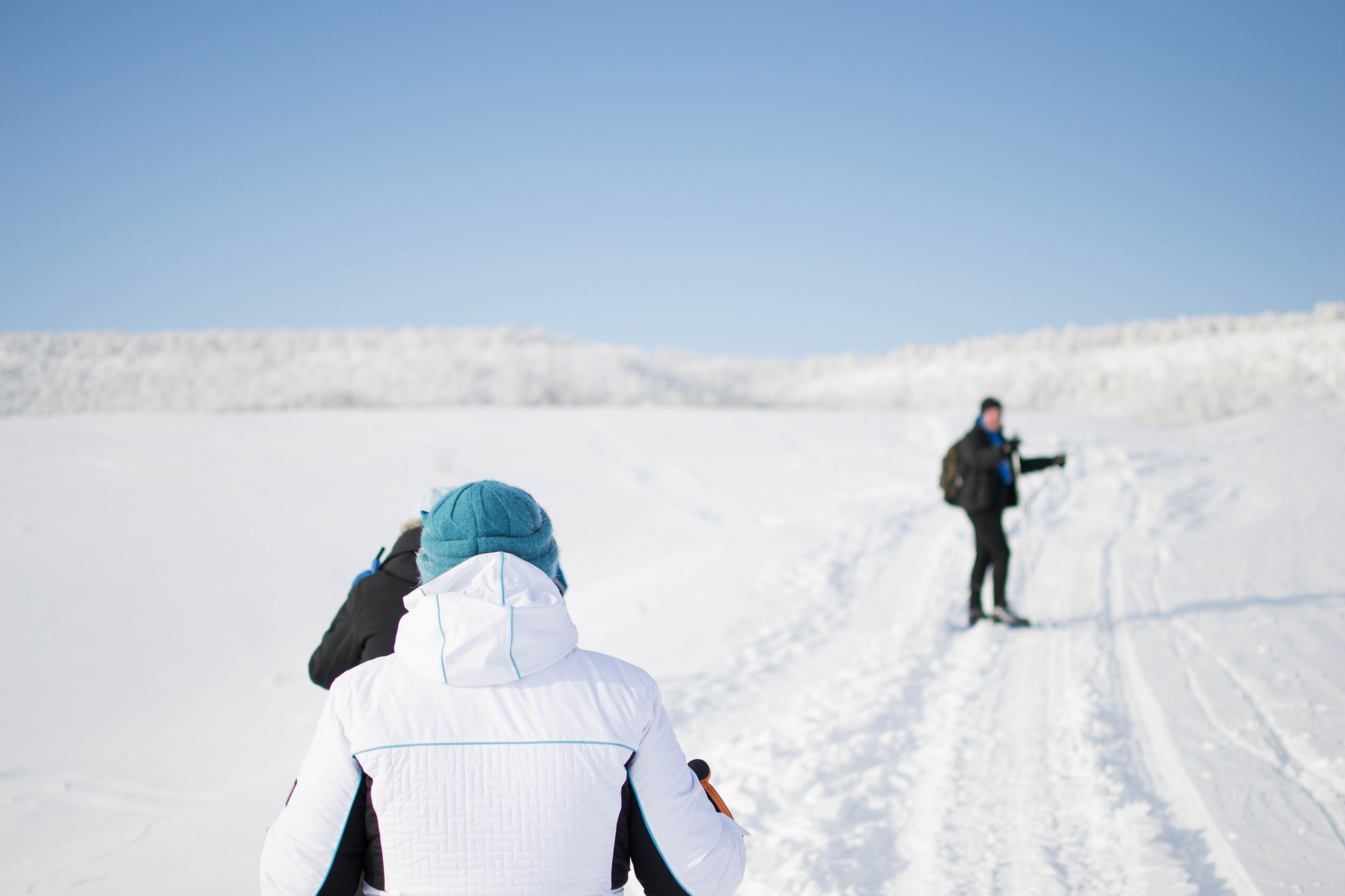 Three people walking through a deserted snowy valley with tire tracks on the ground
