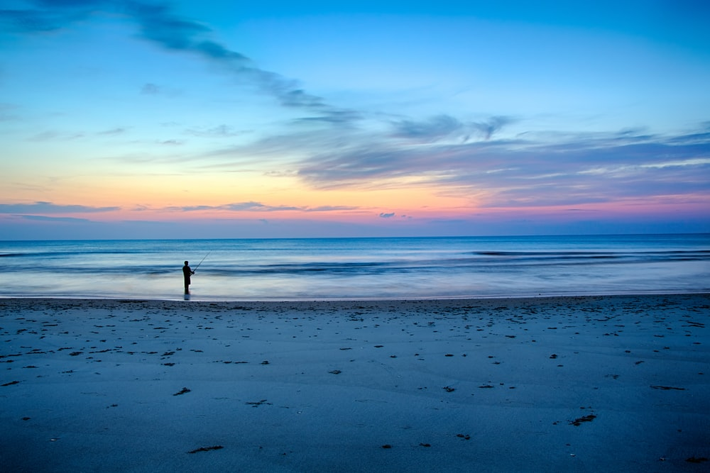 silhouette of person fishing on shallow part of sea