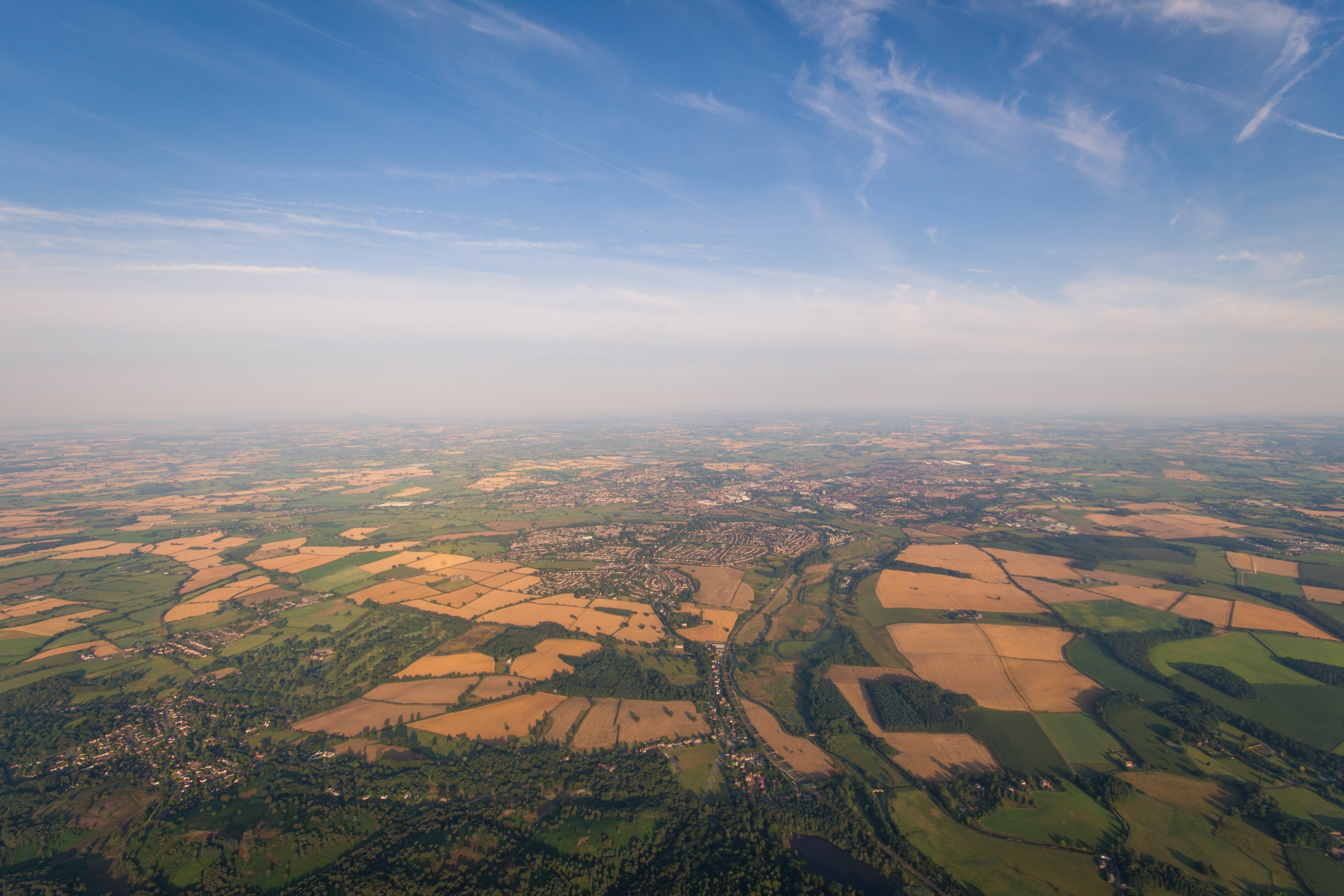 aerial photo of brown and green fields under blue sky during daytime