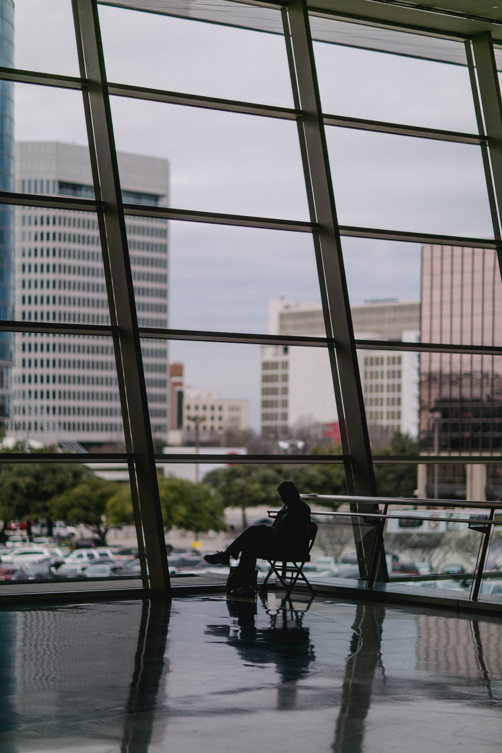 silhouette of person sitting besides clear glass wall inside building