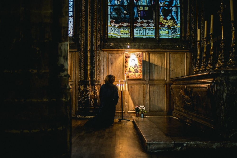 person praying in front of an altar