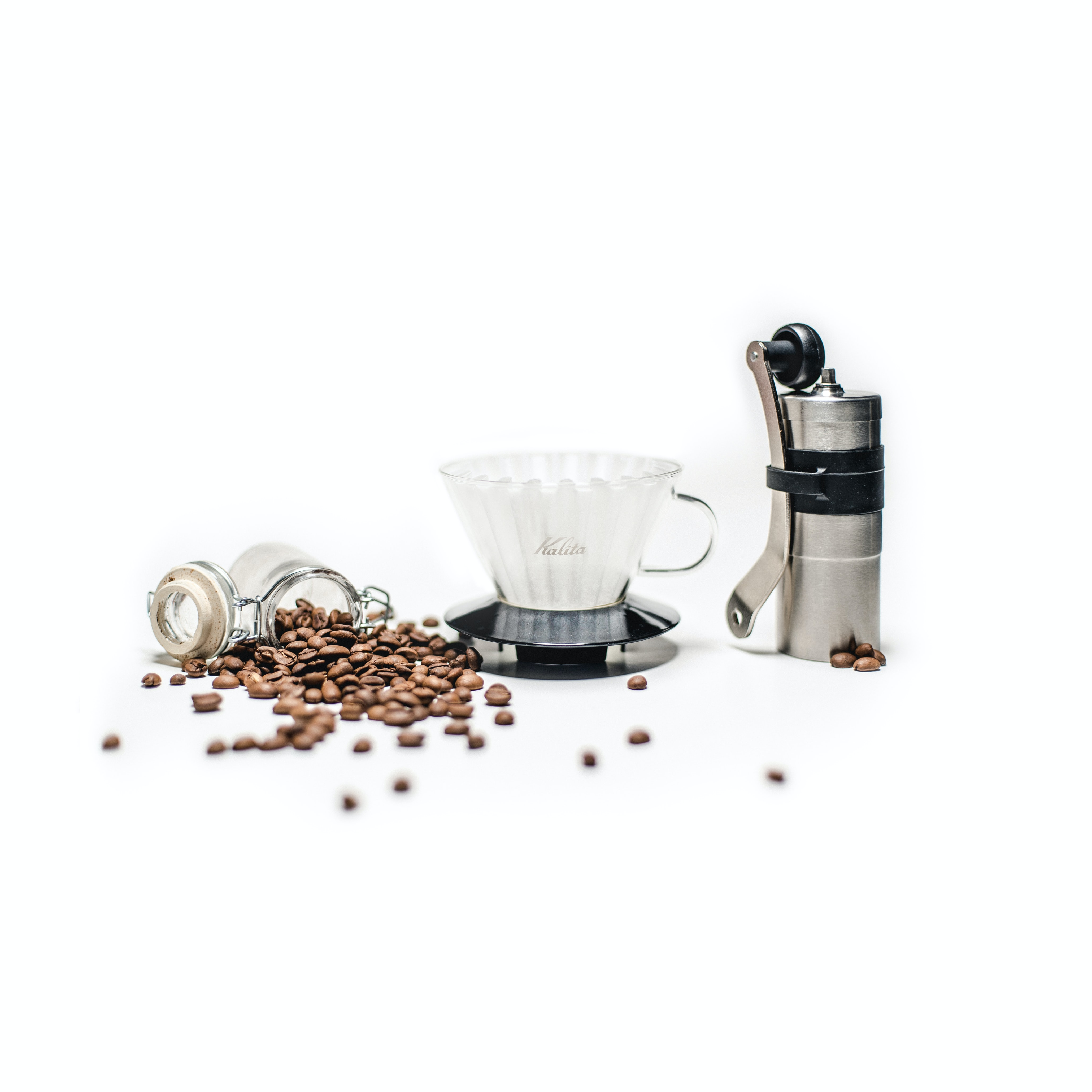 Coffee beans spill out of jar near coffee grinder and mug with filter