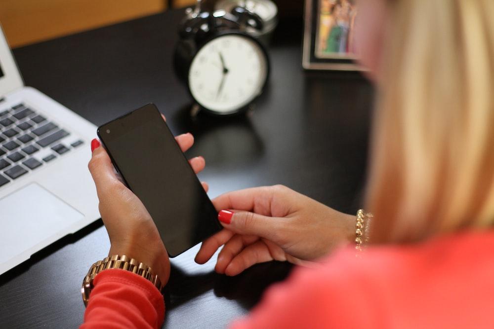woman sitting holding smartphone near laptop