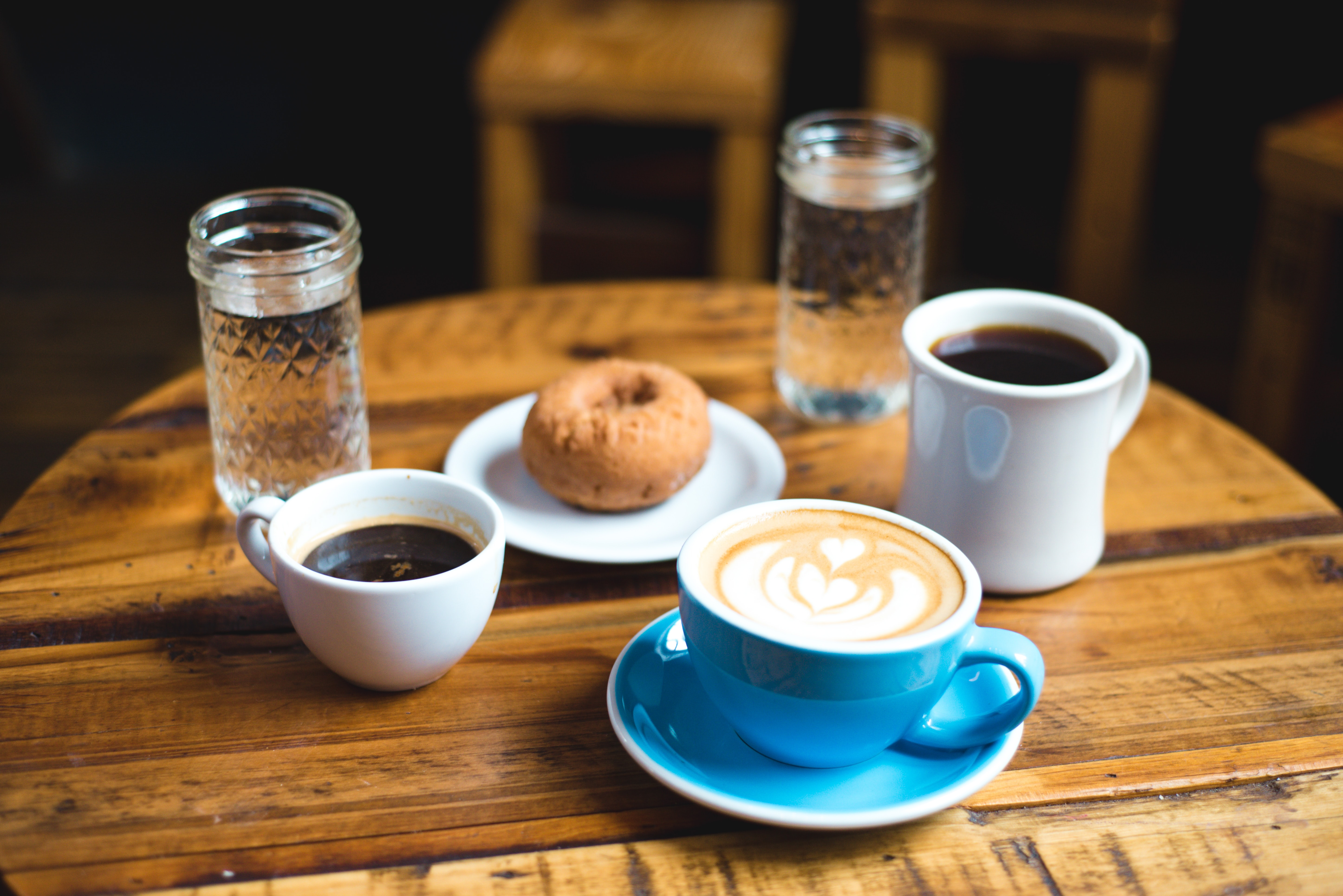 A round coffee table with two cups of black coffee, a latte with an artwork, a donut and water in glasses