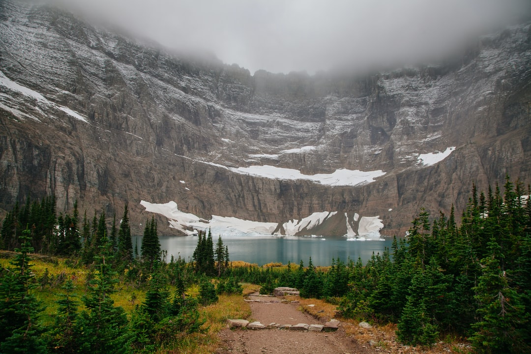 Fog circling above snowy mountains leading down to Iceberg lake surrounded by trees