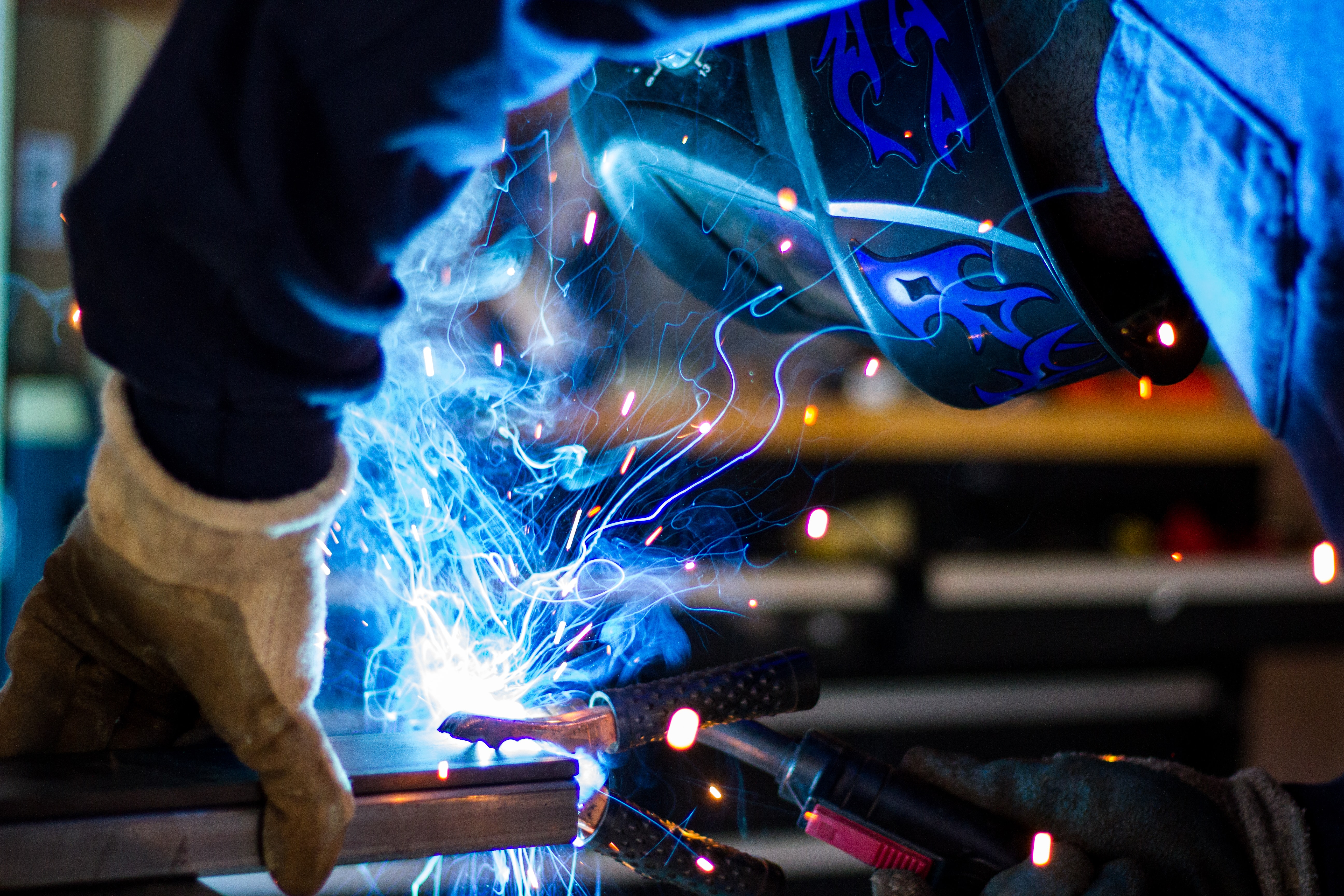 Blue sparks and flames over a piece of metal with a welder leaning over it